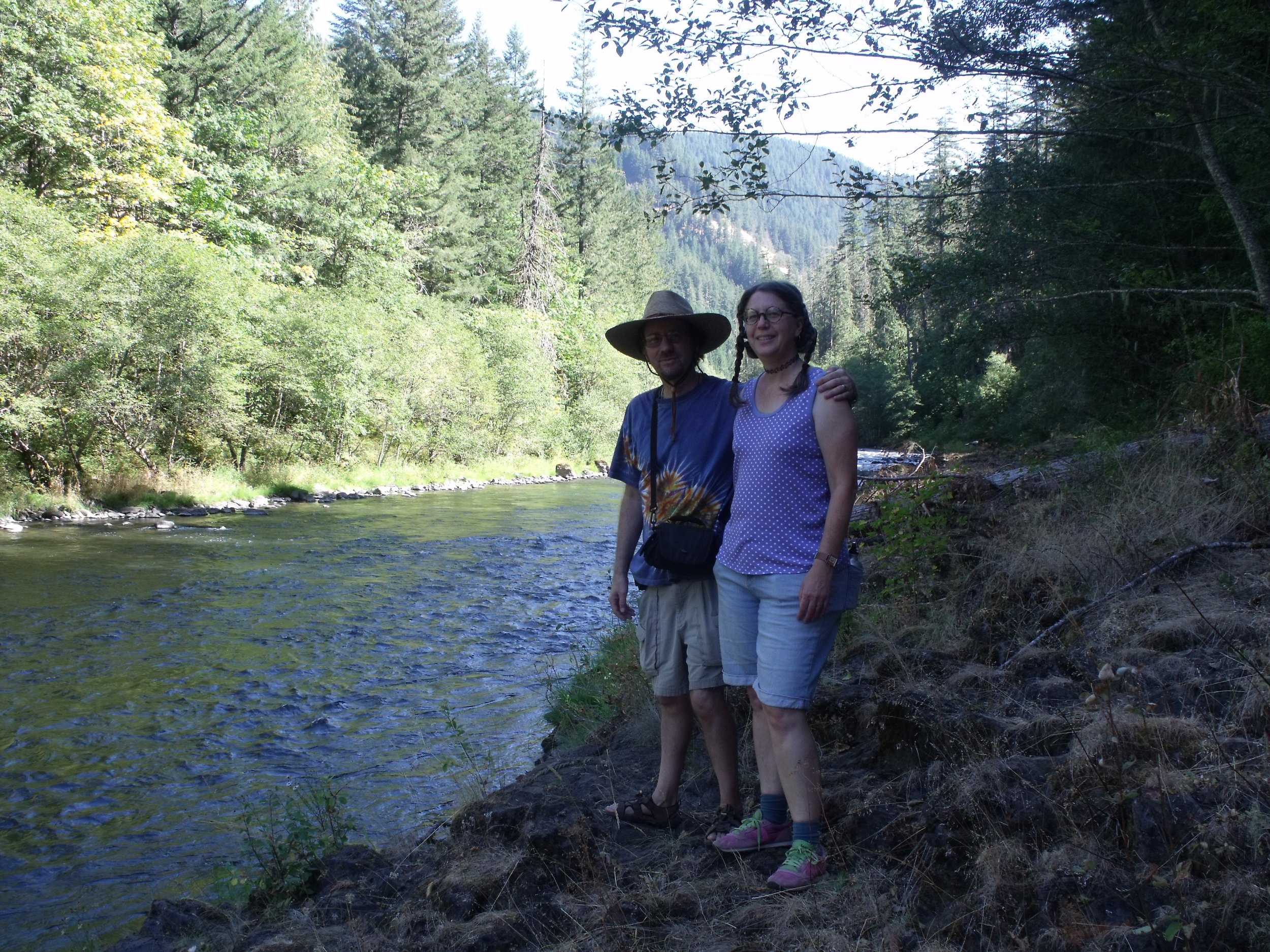 Man and women smiling, stading by a river in a forest.  Husband and Letters of the West illustrator John Maddin and Letters of the West author Michelle Walch along the Clackamas River.