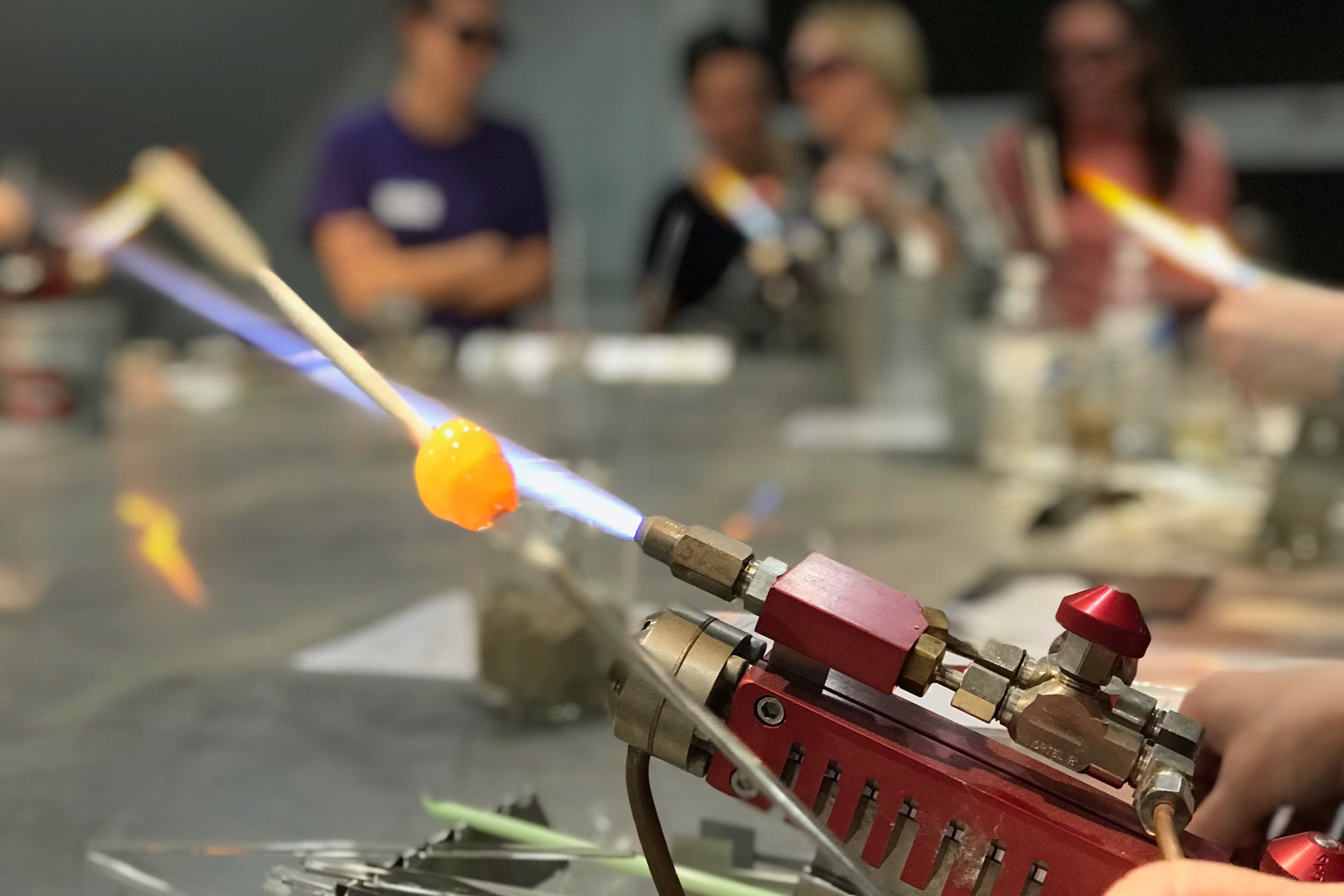 Student using a torch to melt glass and make a bead.