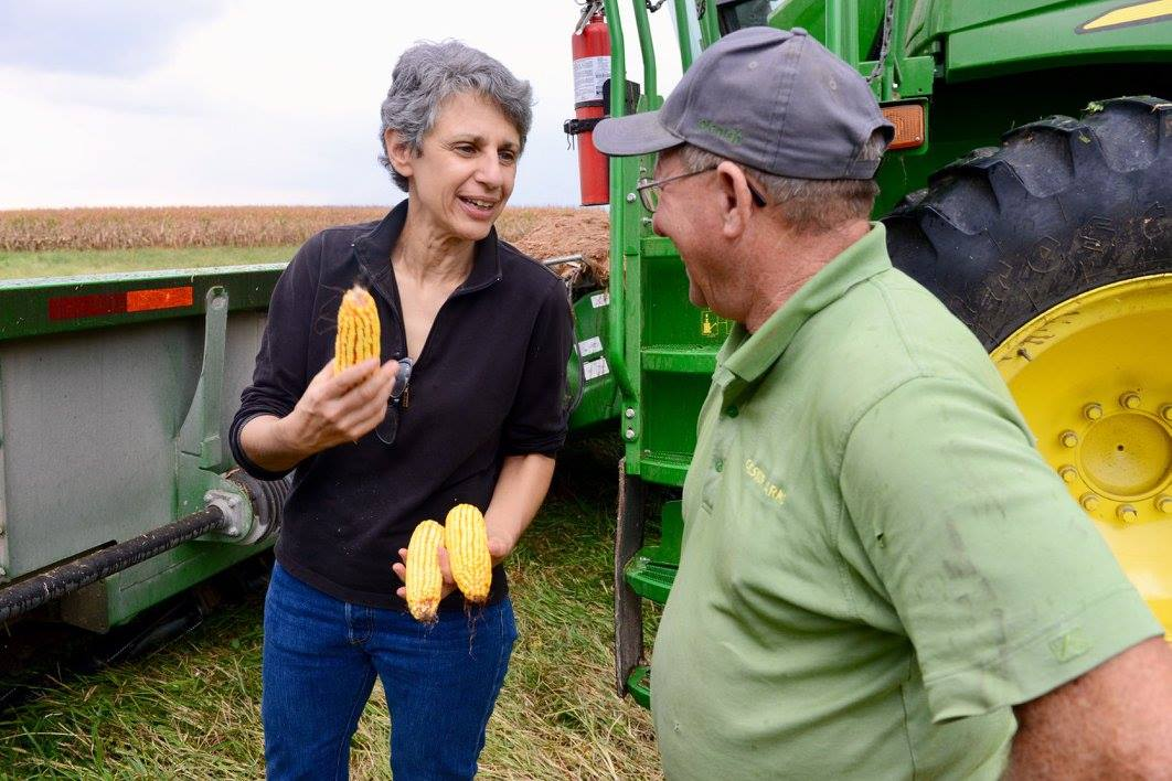 Tamar Haspel holds field corn as Ray Gaesser tells her about the progress of the 2017 harvest.
