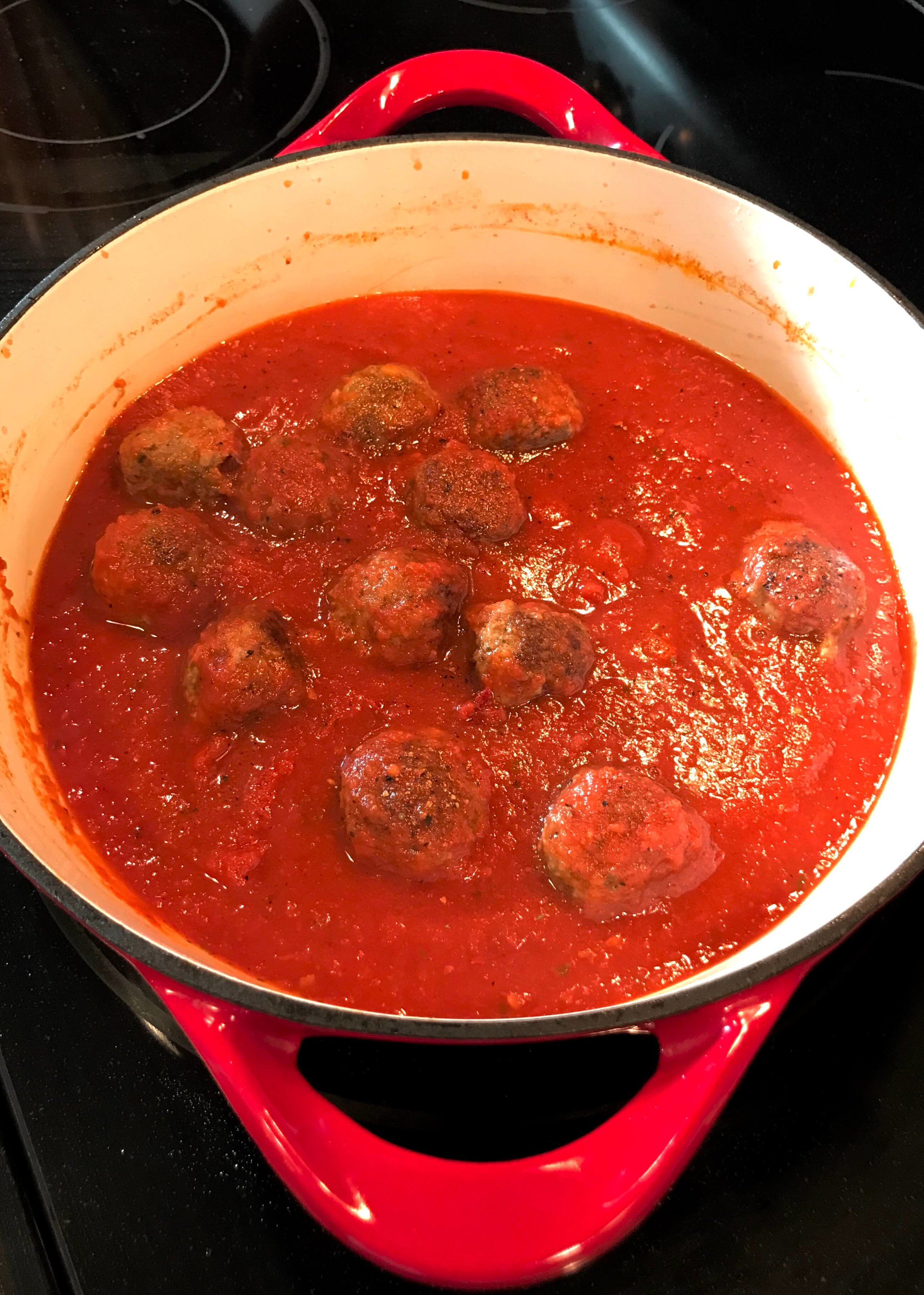 Cook meatballs with sauce on the stovetop.