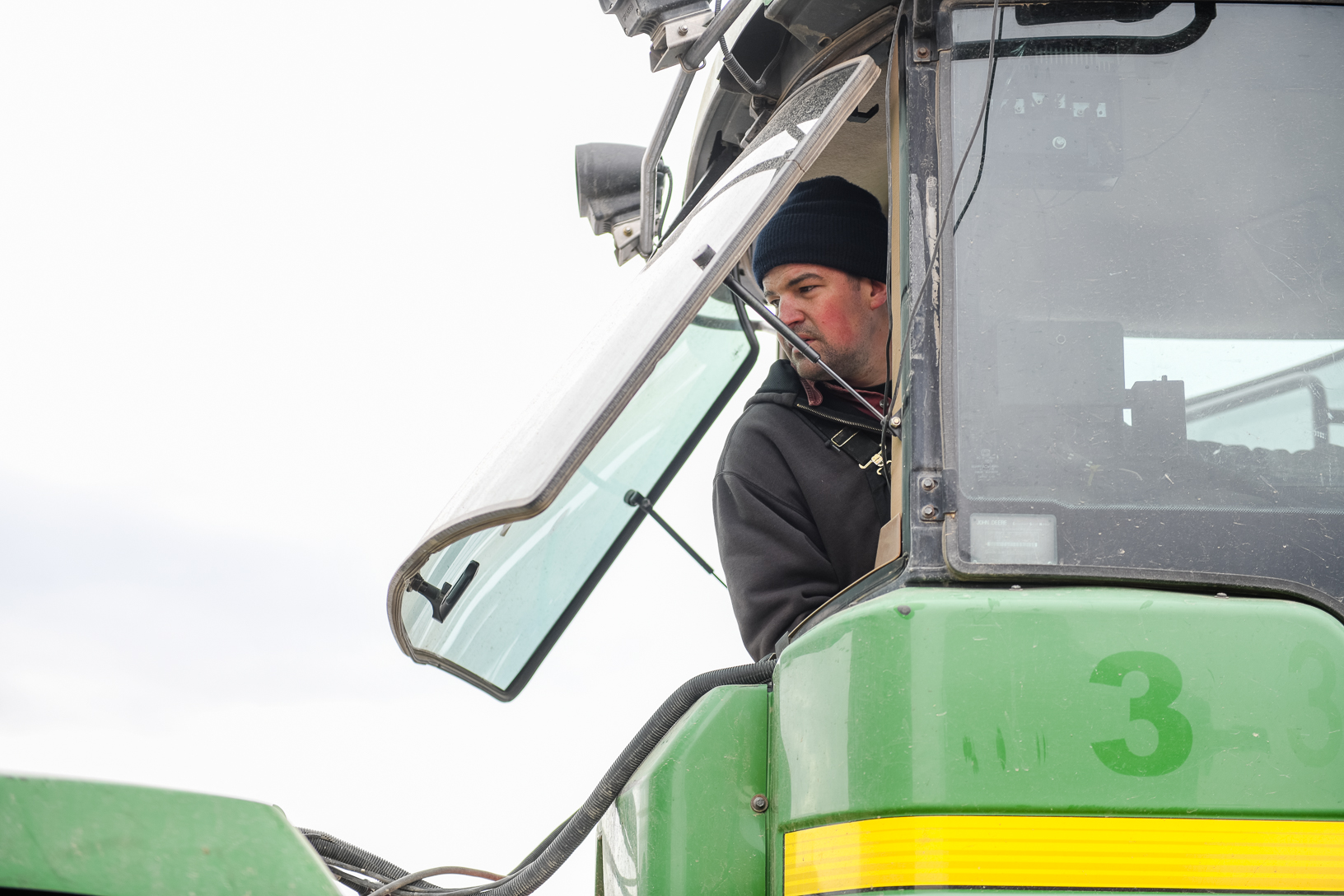 Jake Pyle navigates the tractor while watching the barn move across the frozen soybean field.