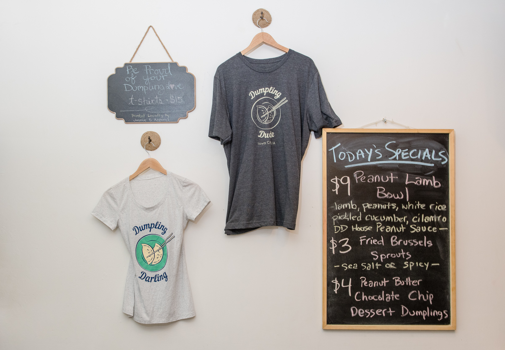 Apparel and menu specials hang on the wall at Dumpling Darling's Iowa City location.