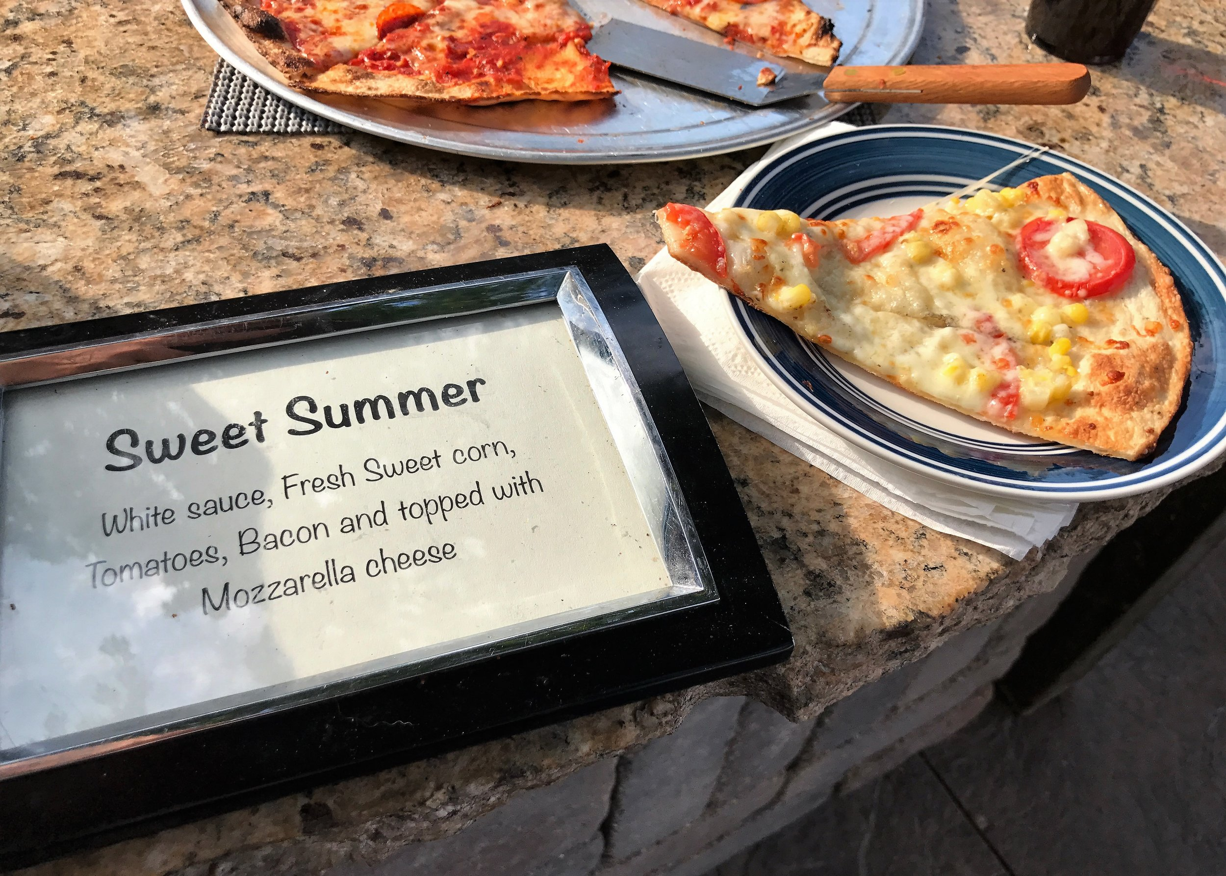 One pizza, in particular, piqued Anita's curiosity: Sweet Summer. Fresh tomatoes, crispy bacon, and tender sweet corn on a wood-fired crust. Photo credit: Anita McVey