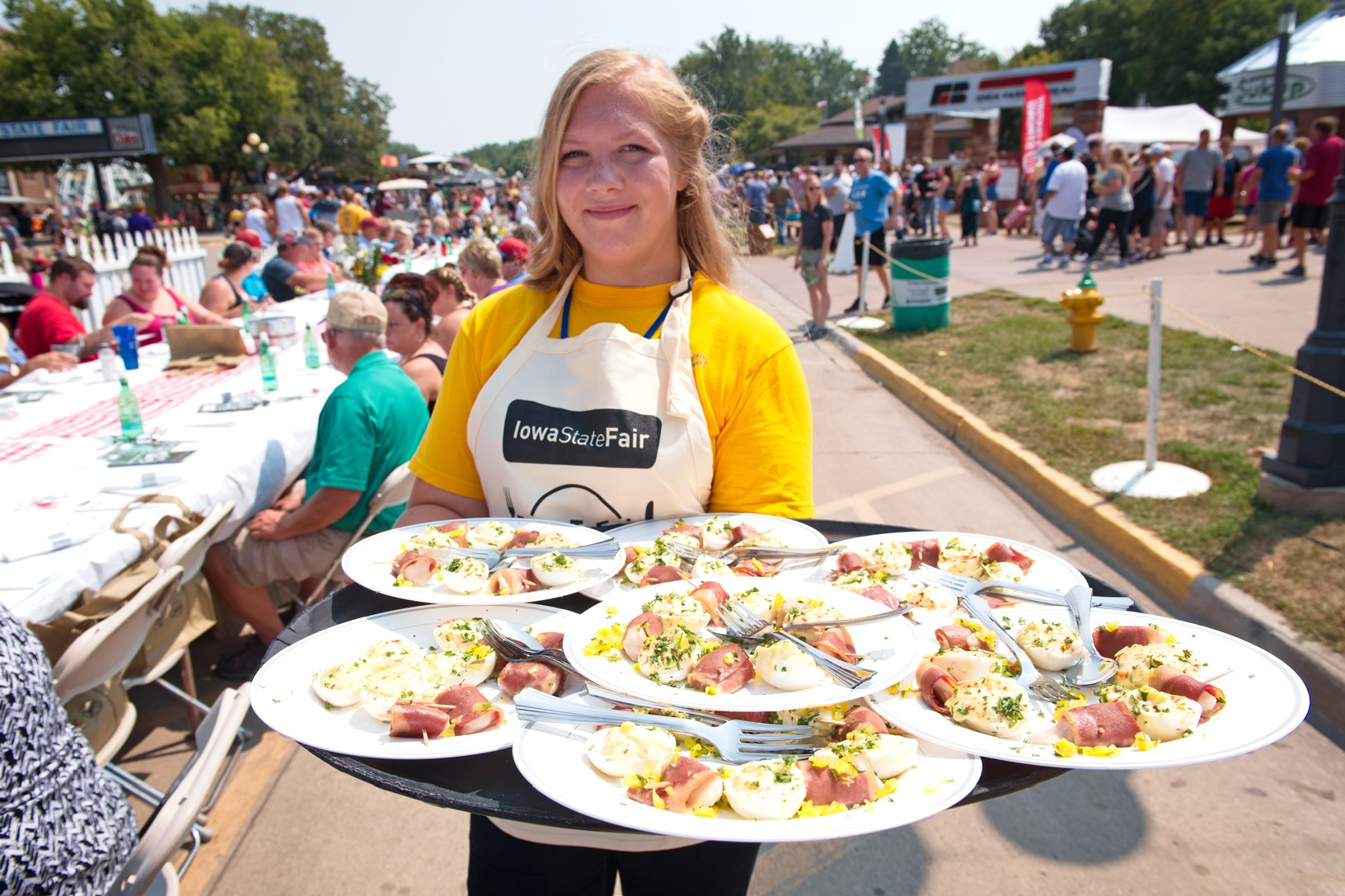 Hailey Bates, ACGC FFA, prepares to serve food to the participants of the first Farm to Table event at the Iowa State Fair. Bates and other FFA students helped serve the food that had ingredients from all of Iowa's commodity groups. Photo credit: Joseph L. Murphy/Iowa Soybean Association