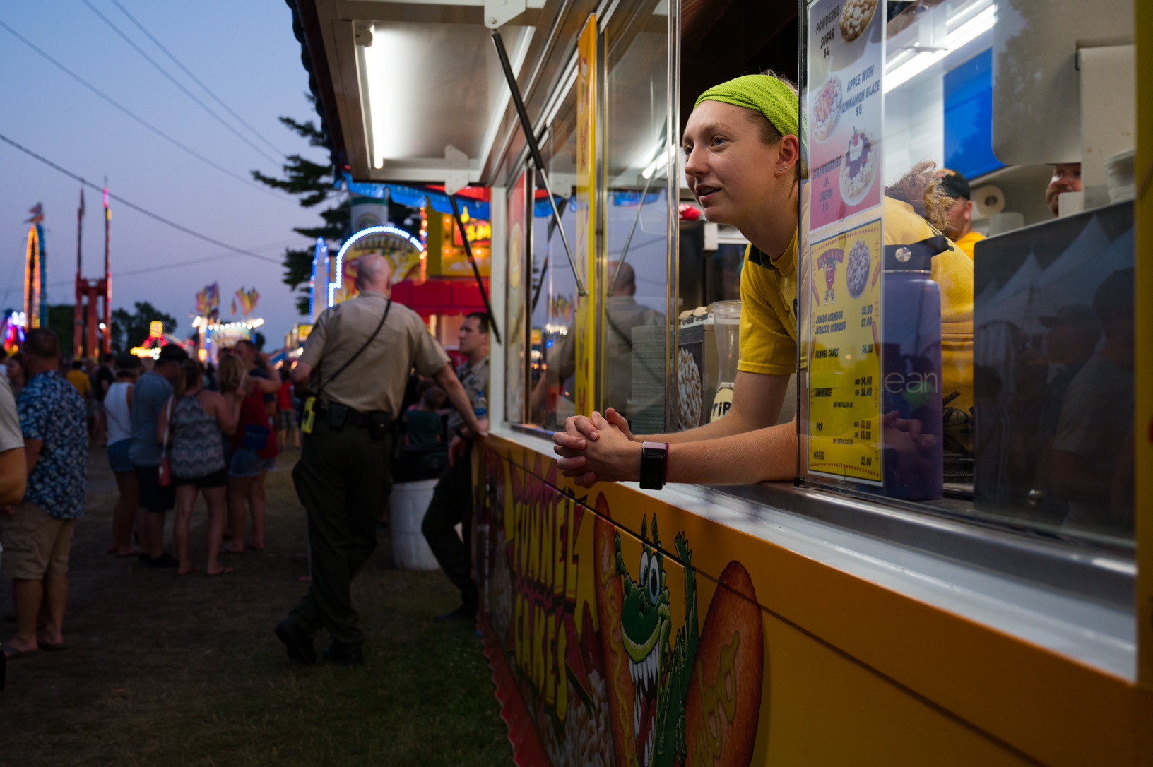 Kaelee Knoll sings along with a Hootie and the Blowfish song while waiting for customers at a funnel cake stand during the Jones County Fair. Photo credit: Joseph L. Murphy/Iowa Soybean Association