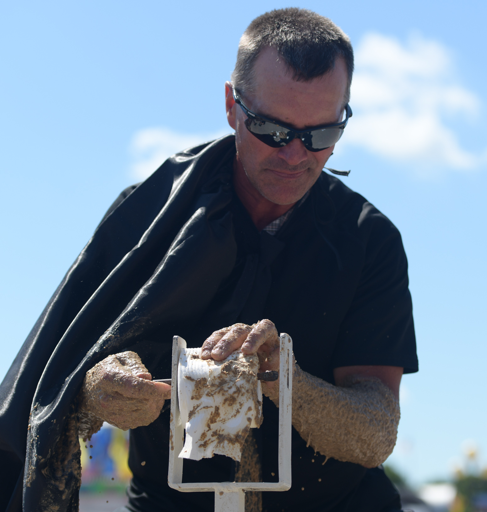Dave Moses, of team Space Balls, tries to thread a roll of toilet paper onto a toilet paper holder during the Outhouse Race at the Iowa State Fair. Photo credit: Joseph L. Murphy/Iowa Soybean Association