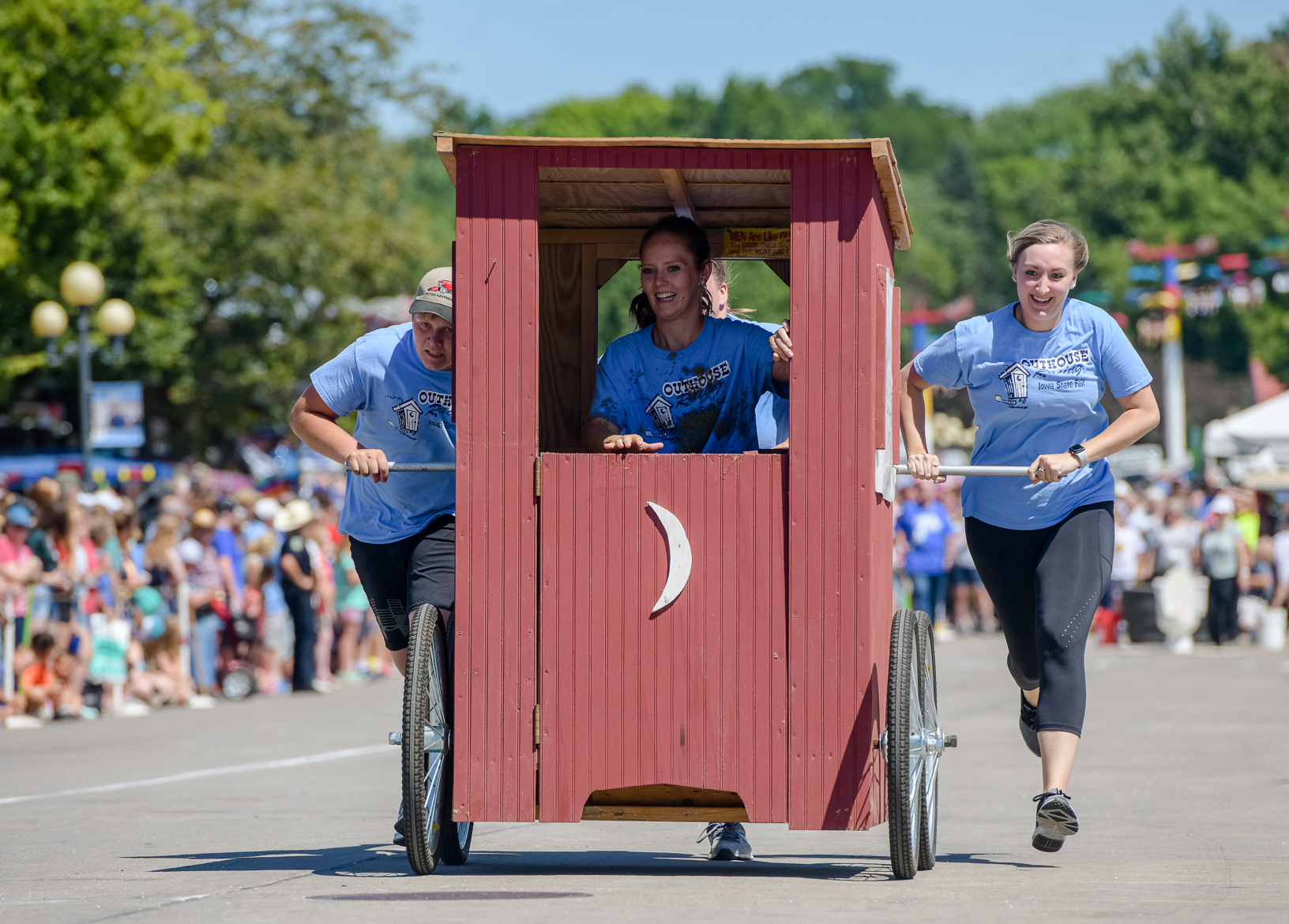 A team competes in the outhouse race on the Grand Concourse of the Iowa State Fair. The outhouse race is where teams create home-made outhouses on wheels and compete in a relay race. Photo credit: Joseph L. Murphy/Iowa Soybean Association