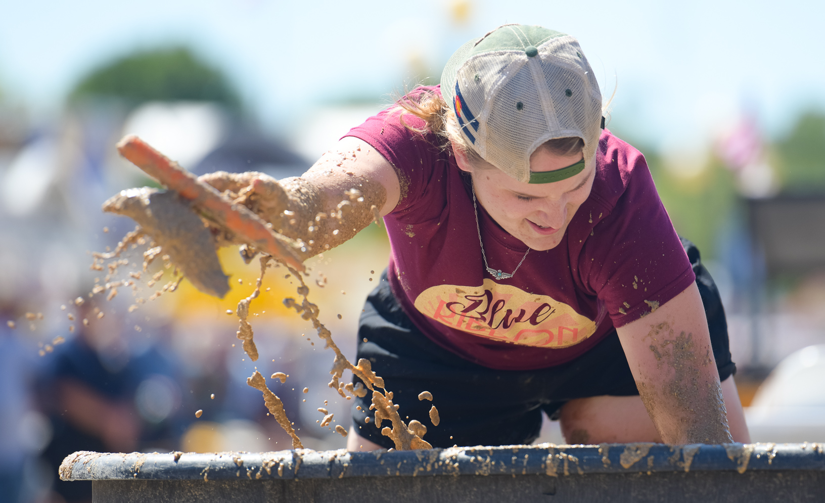 Lucia Ruppert looks through slop for a corn cob while competing in the Outhouse Race at the Iowa State Fair. Photo credit: Joseph L. Murphy/Iowa Soybean Association