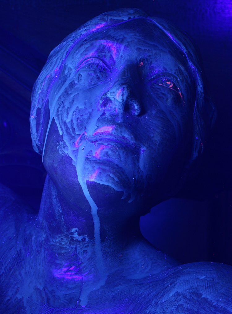 Photo of a mahogany sculpture taken under UV light clearly revealing excessive wax deposits