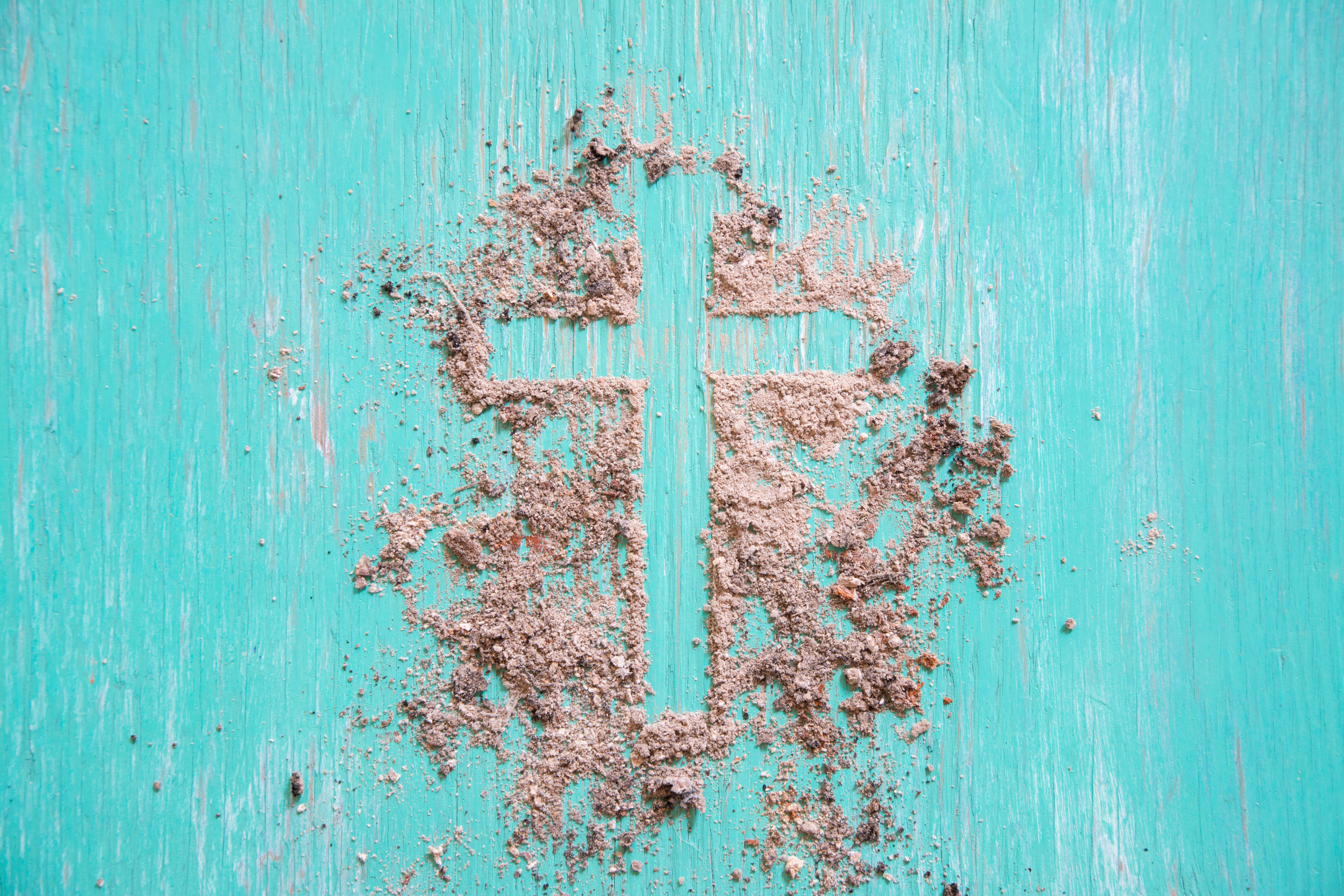 Cross in sand on teal wood.jpeg