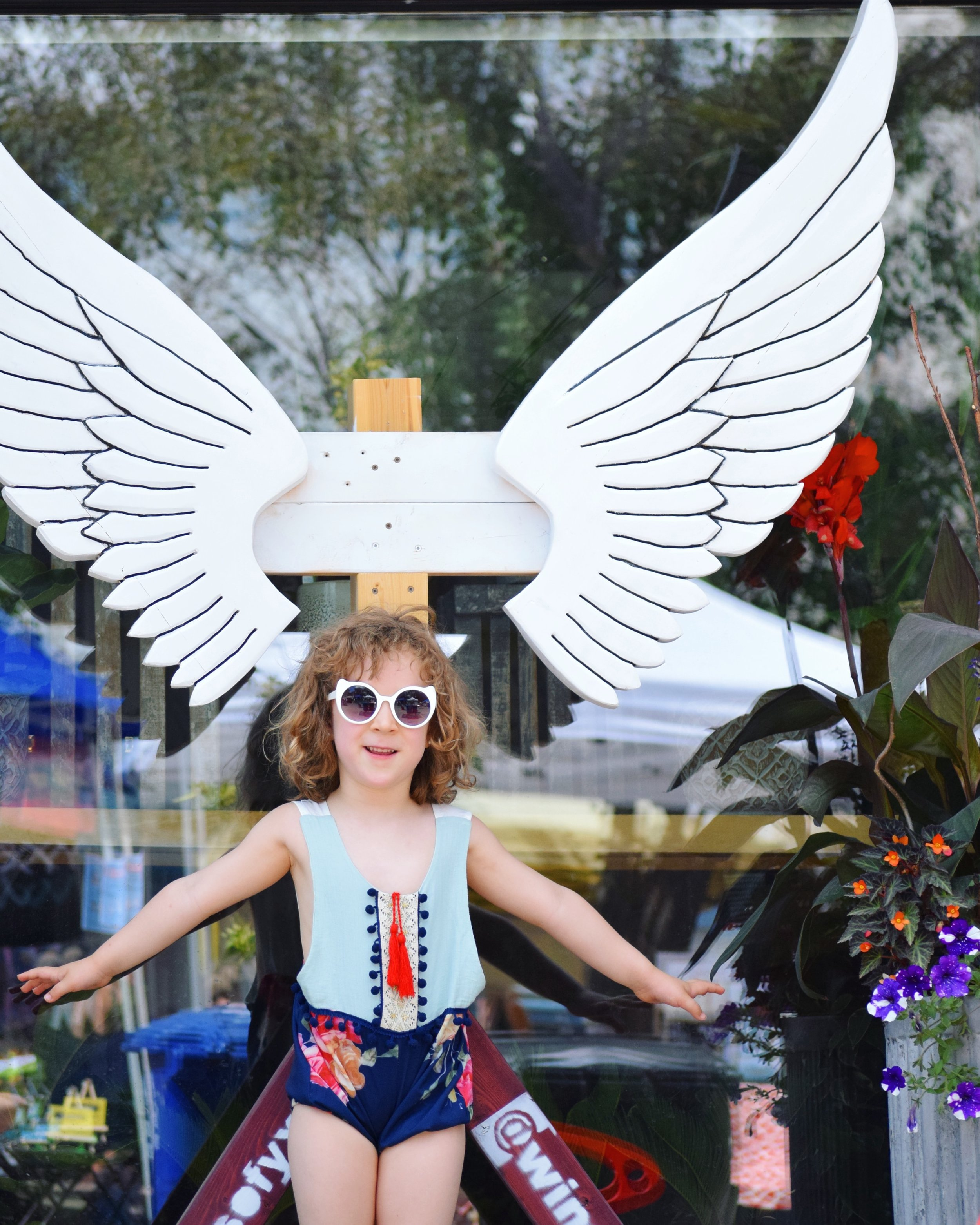 My daughter poses with a set of wings during the Fringe Festival on Broadway.