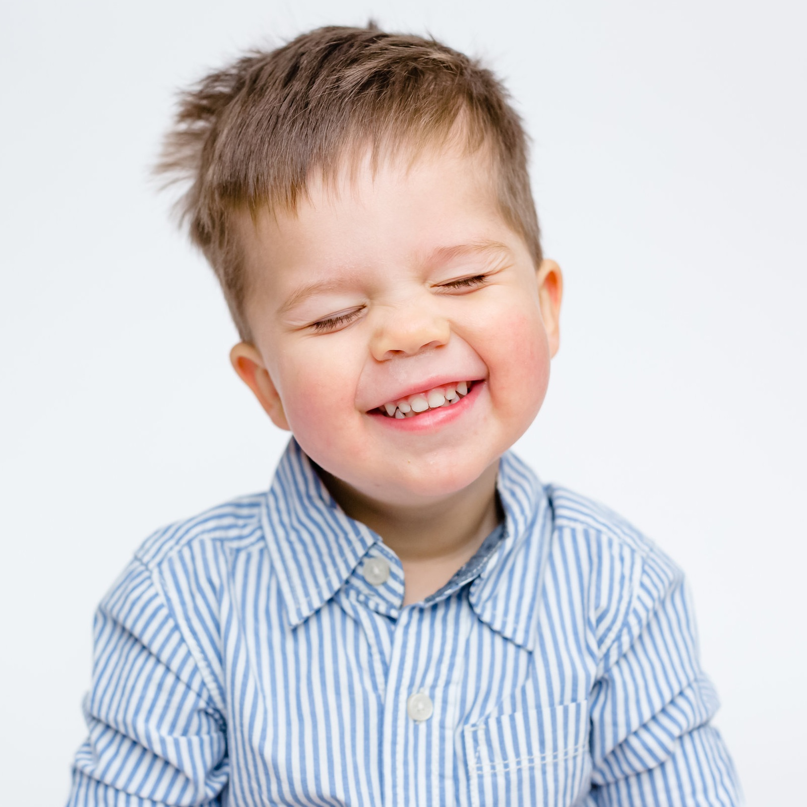 modern preschool candid squint smile boy portrait