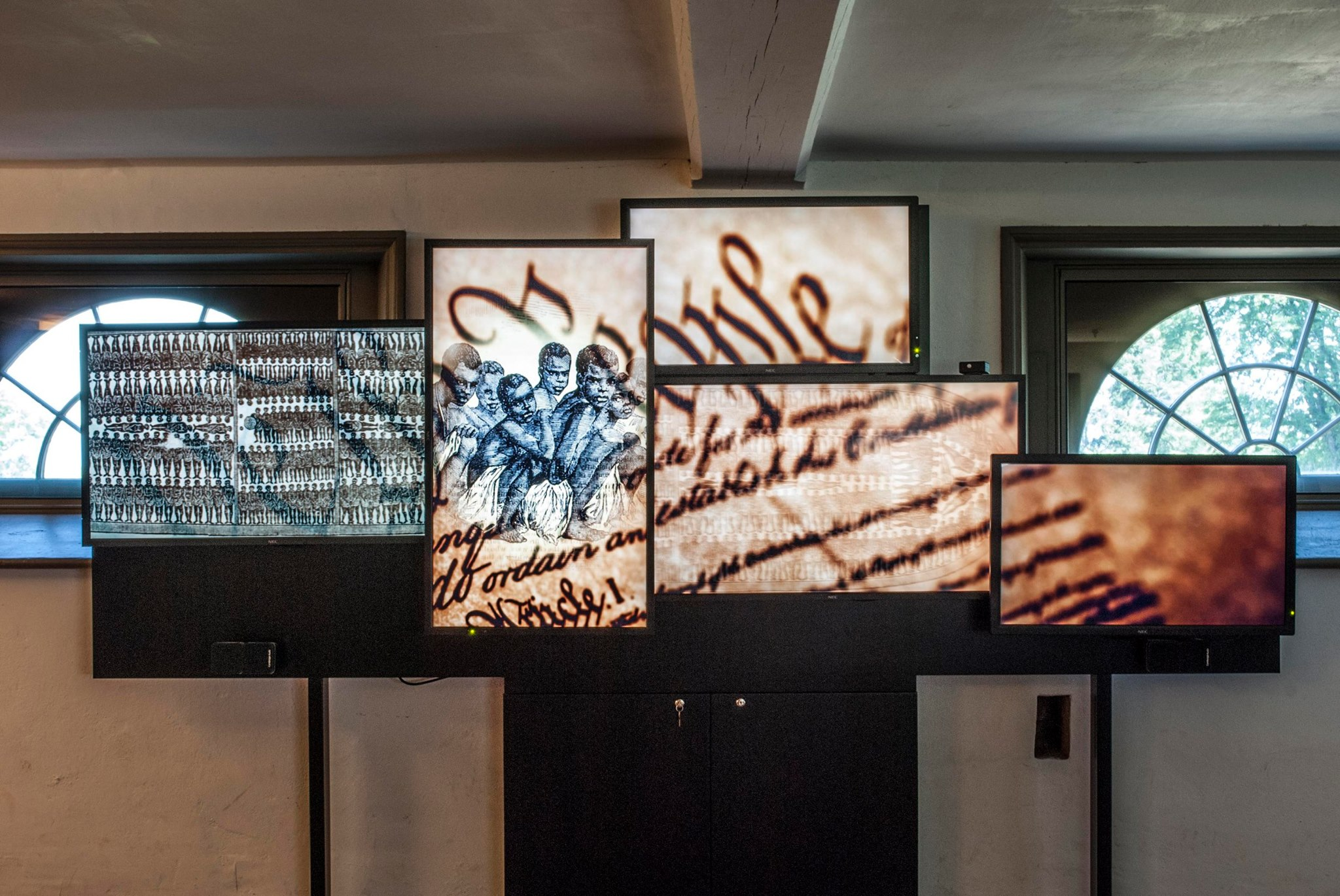 Multimedia display with video mapped to screens featuring rolling content and a historical journey through the cost of slavery.