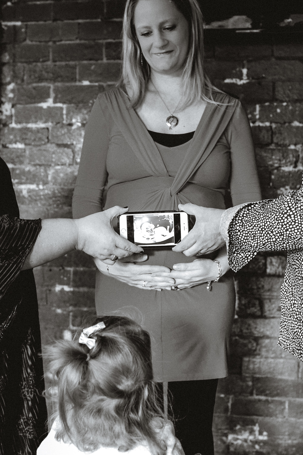 surrogate and daughter, intended parents sharing scan at maternity session