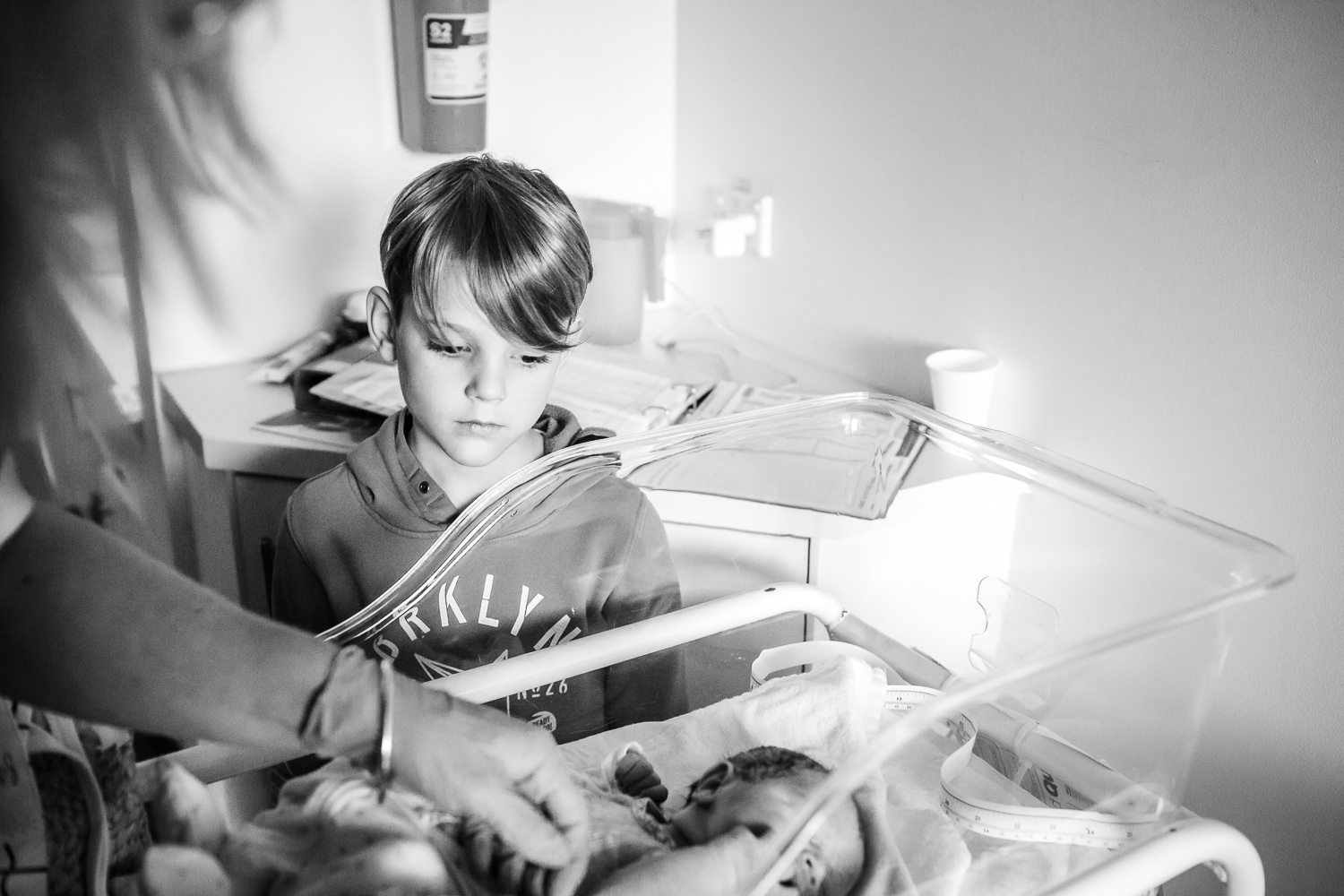 baby being dressed in hospital while brother watches on