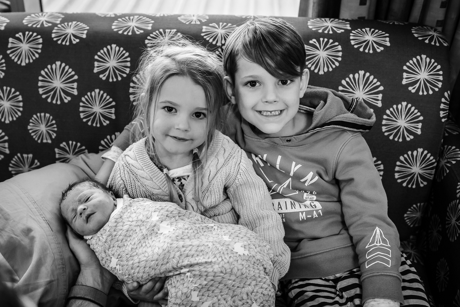 first photo of all three siblings sitting on couch
