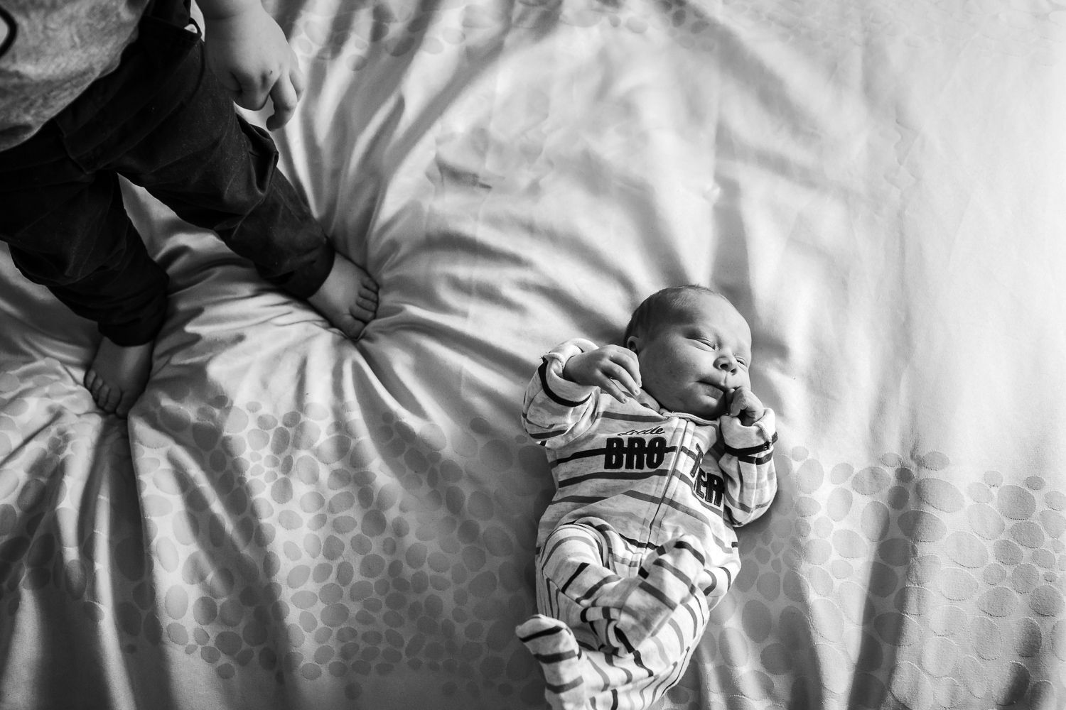 big brothers feet and little brother on bed during newborn lifestyle session, Melbourne
