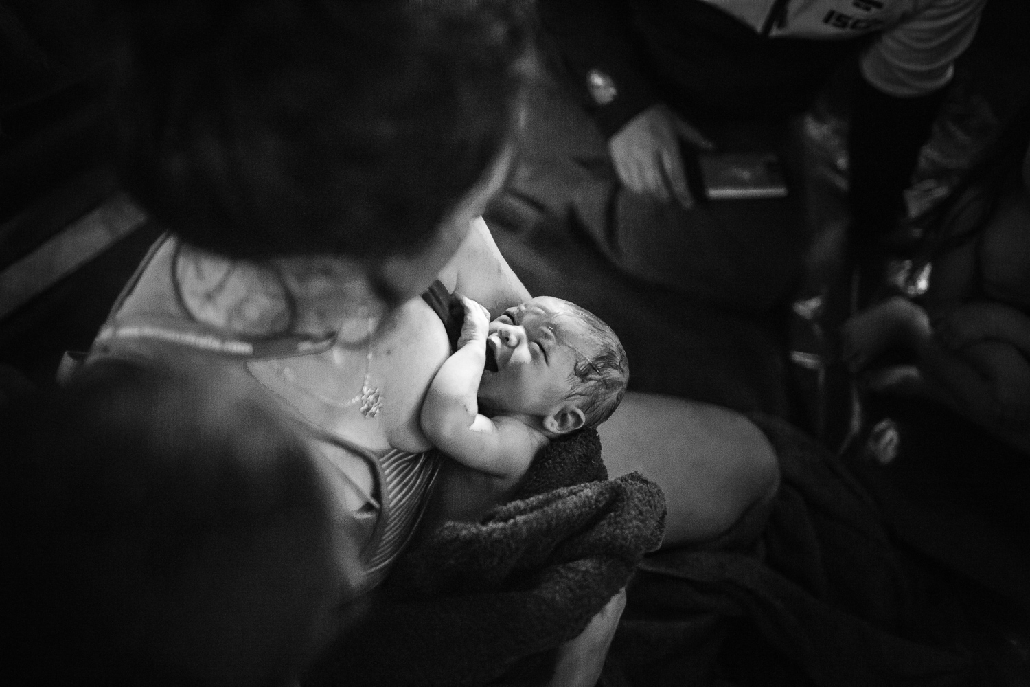 Newborn baby looking up at mother for the first time captured by Melbourne Birth Photographer, A Grateful Heart.