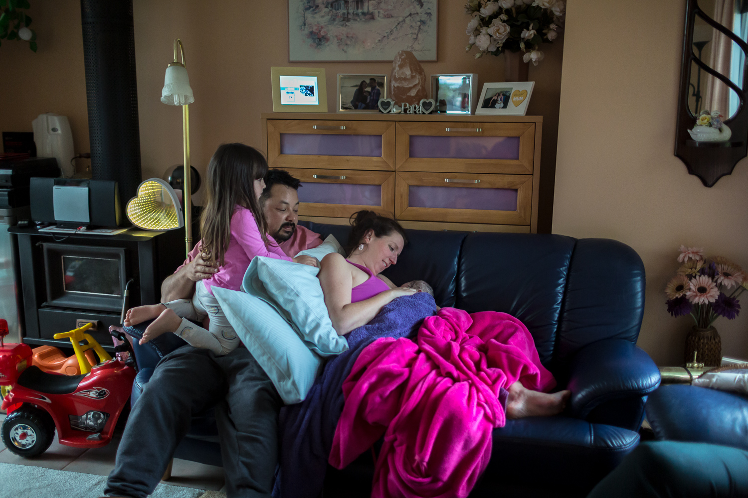 Whole picture birth. Family on couch soaking in the details of newborn baby in the golden hours after birth.