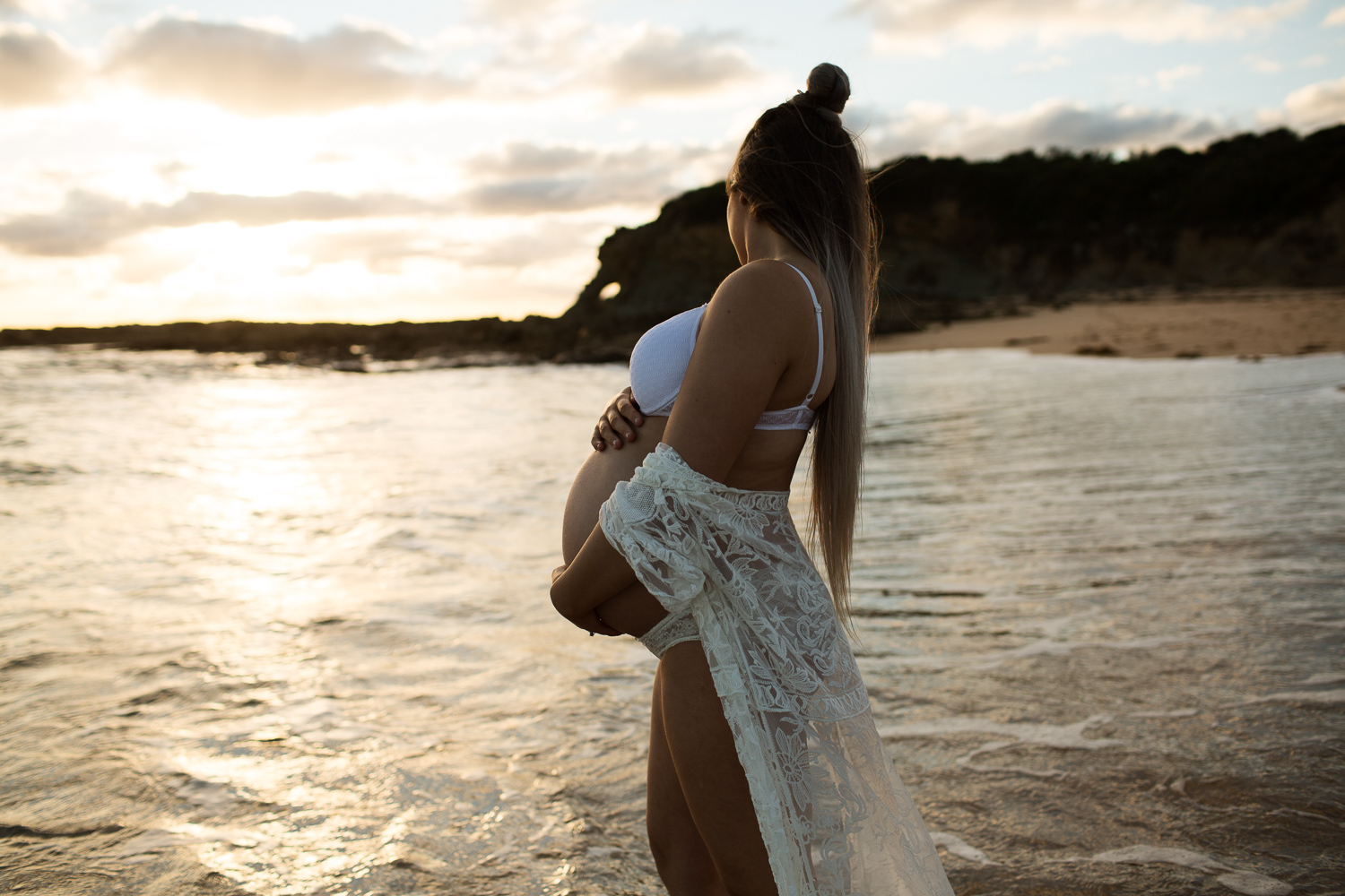 expectant mother holding her belly while standing in the water during golden hour. Her long her is down her back and she is looking away from Amy from a greatful heart photography.