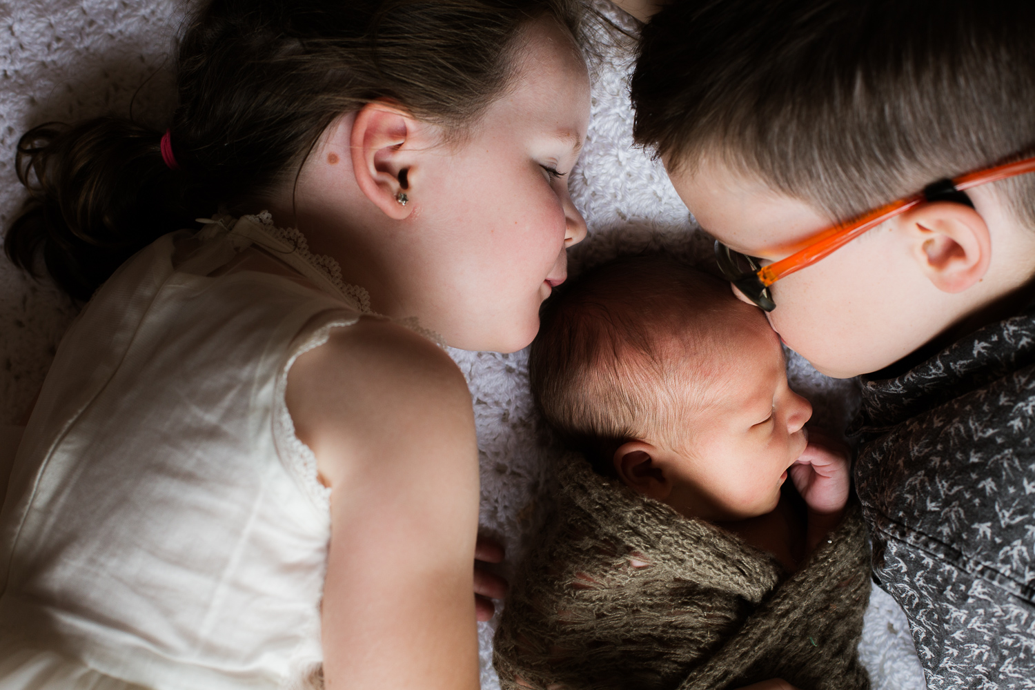 siblings kissing newborn during lifestyle family session at home in Mornington