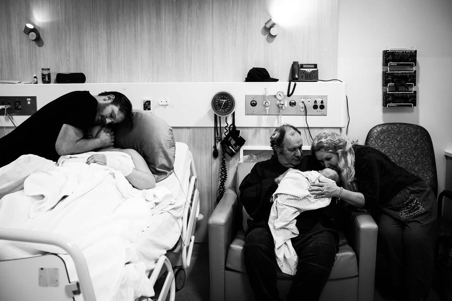 mother and father hugging on hospital bed while grandmother and grandfather hug and kiss newborn baby on chair.