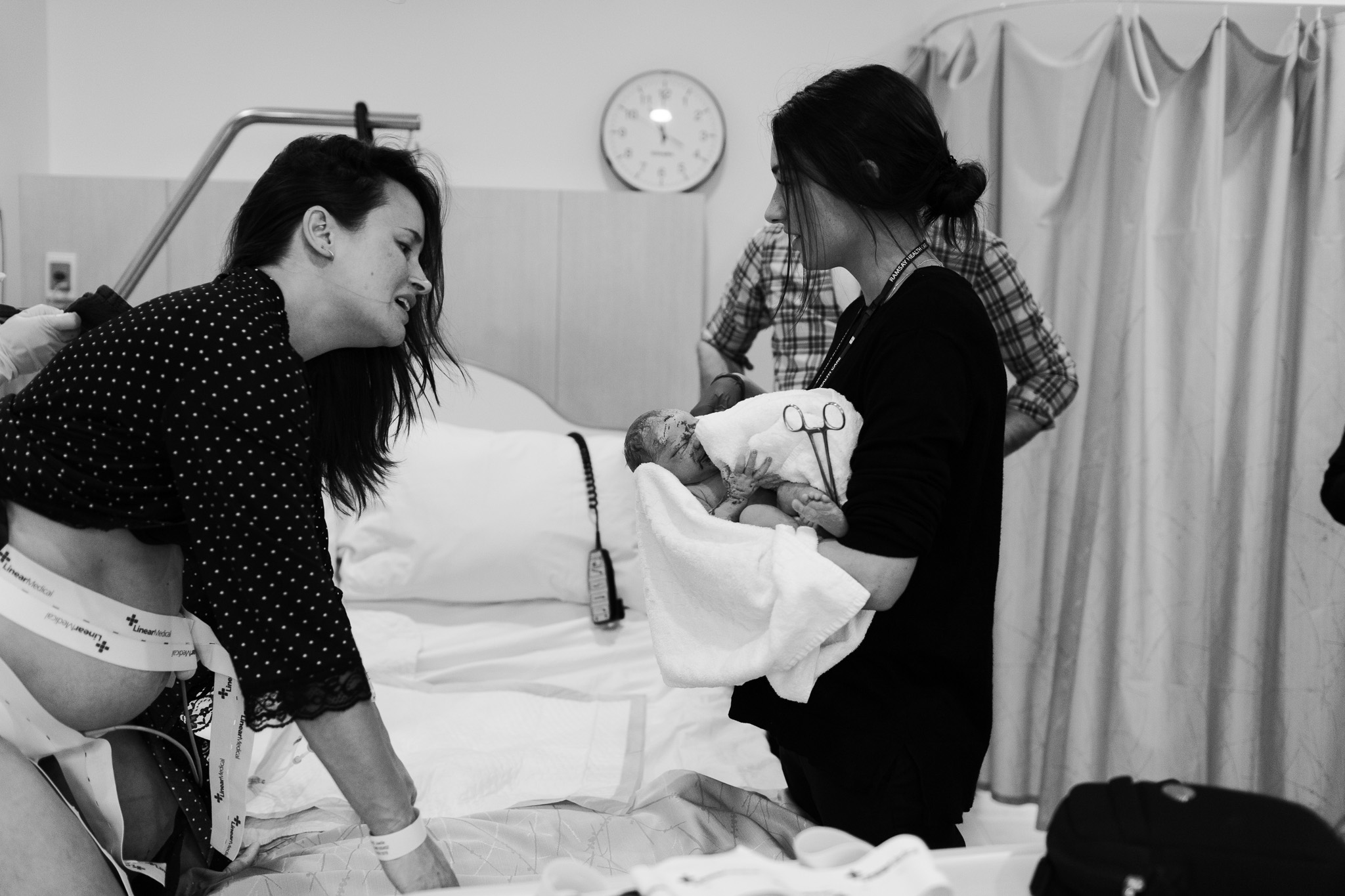 Love at first sight. Mother looking at newborn for the first time after fast birth at melbourne hospital as captured by melbourne birth photographer.