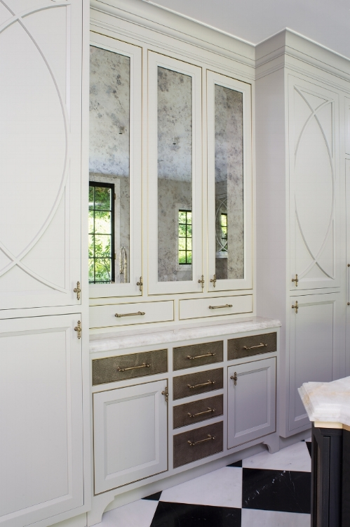 Deco inspired, brass trimmed openings highlighted with antique mirror