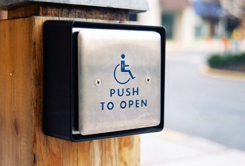 An external silver accessibility button which reads push to open