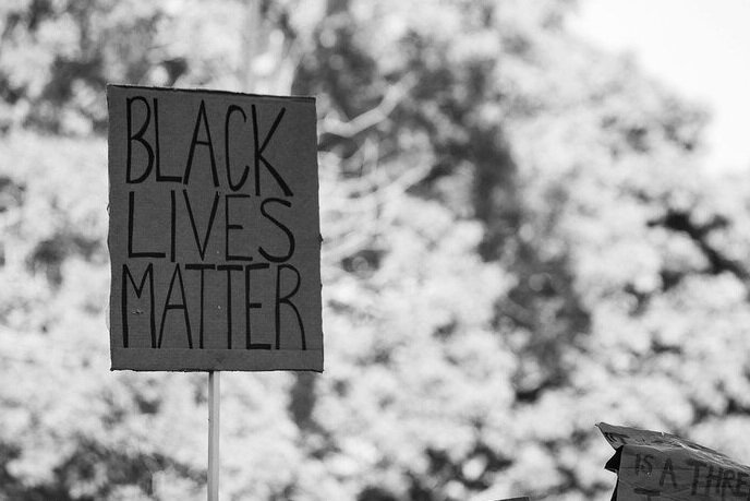 "A black and white photo depicts signs at a Black Lives Matter protest. The primary sign reads ""Black Lives Matter."""