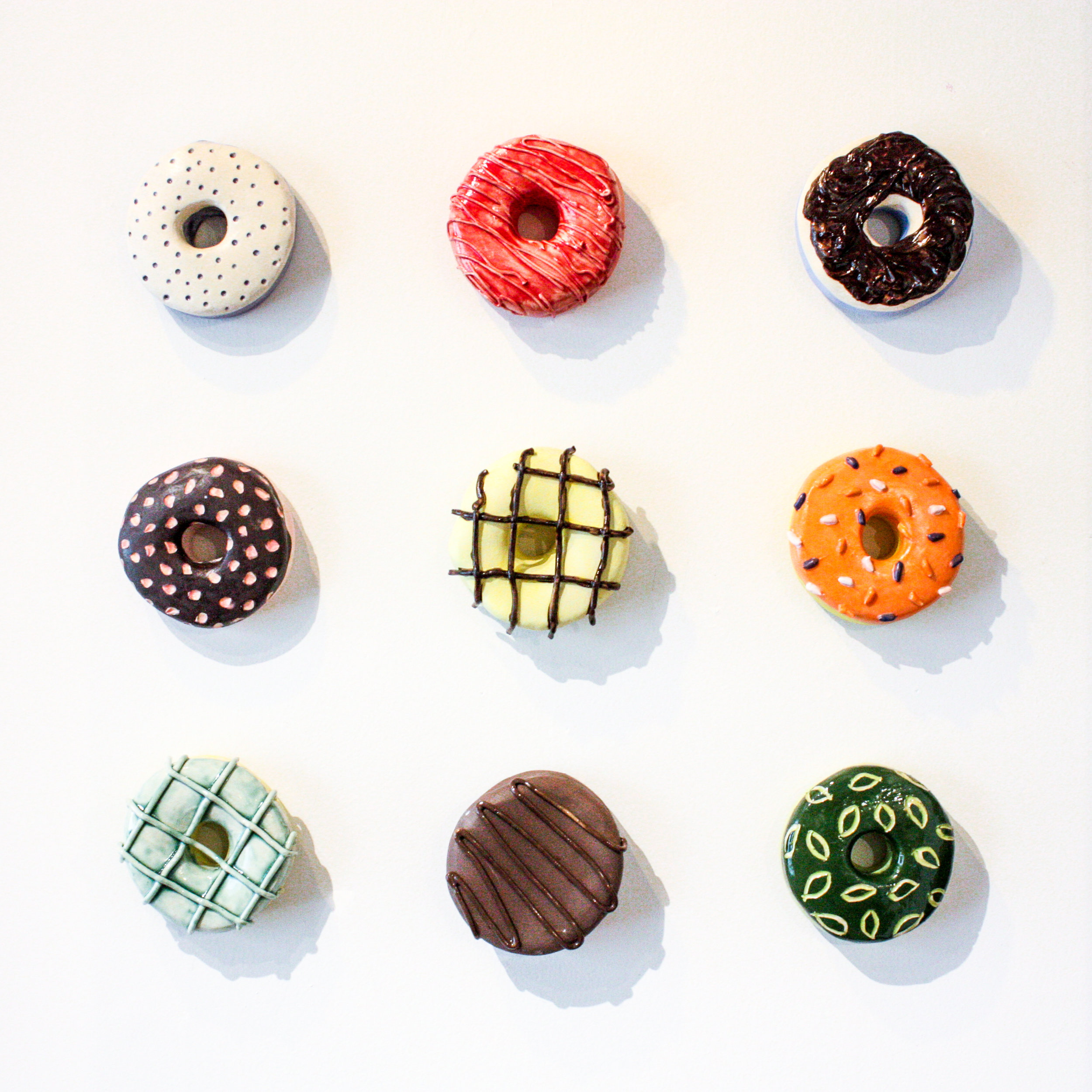 """Spring Mix Donut Set - Nine 5"""" x 5"""" donuts, 18"""" x 18""""Stoneware clay and ceramic glazeSOLD"""