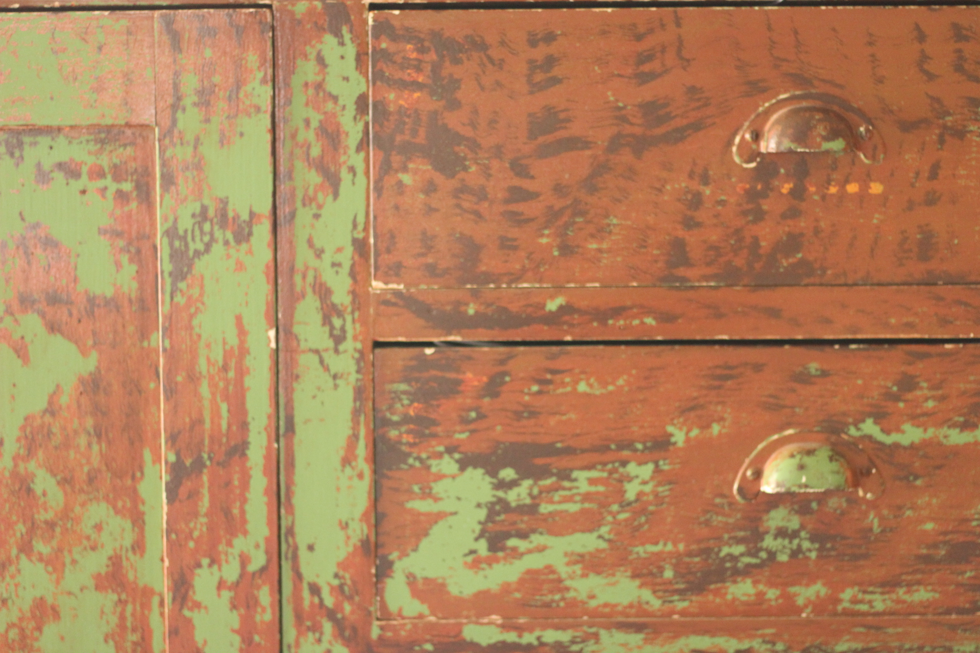 This piece is a mystery. Its a large dresser -- five feet tall and seven feet long -- with eight drawers to the right and a wardrobe on the left. It's made of poplar and weighs more than I can handle. We bought it to put in an upstairs room. When we got it home we realized it would never make it up the stairs.   It was once a built in. We know this because there is finish trim on one end and none on the other. It's not missing. The other end wasn't built to take it.   Poplar was traditionally painted and I suspect the this piece has always been painted. The earliest visible coat is bright green. Beneath every drawer pull there is a line of seven orange dots.  The top coat of paint is a dark red -- almost brown -- that has been crudely and wonderfully grained in a bold loose pattern. There is wear in all of the right places -- around the pulls, the edges and the wardrobe door.   (The drawer edges are as crisp as the day it was built. One of my many pet peeves is often found in distressed furniture finished by mis-guided painters. So other drawer edges are sanded round to indicate wear. There isn't more protected surface than the top of drawer that is inside a case most of its existence. Unless the piece was used in some unusual way - drawer edges should be clean and square. Rant over)  The mystery is the faux graining over the green surface. The green seems more modern that that grain finish. I would love to know its story. A store fixture? Lodge fixture? Just a big dresser at home?