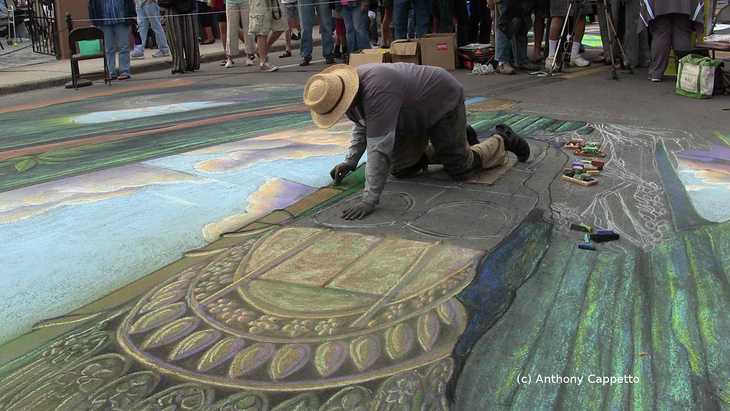 An artist on their hands and knees building up and detailing among an audience of thousands...