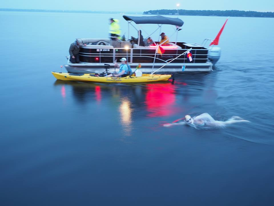 Tackling a swim at dusk with her team's support. PC: Ken Classen.