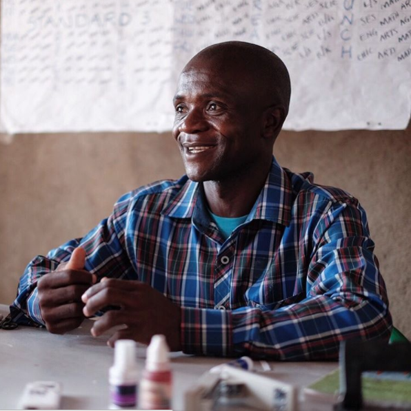 Our model taps into the energy and dedication of education leaders like this one, who grades compositions in the brightest corner of his classroom in a low-fee community school in Nairobi.