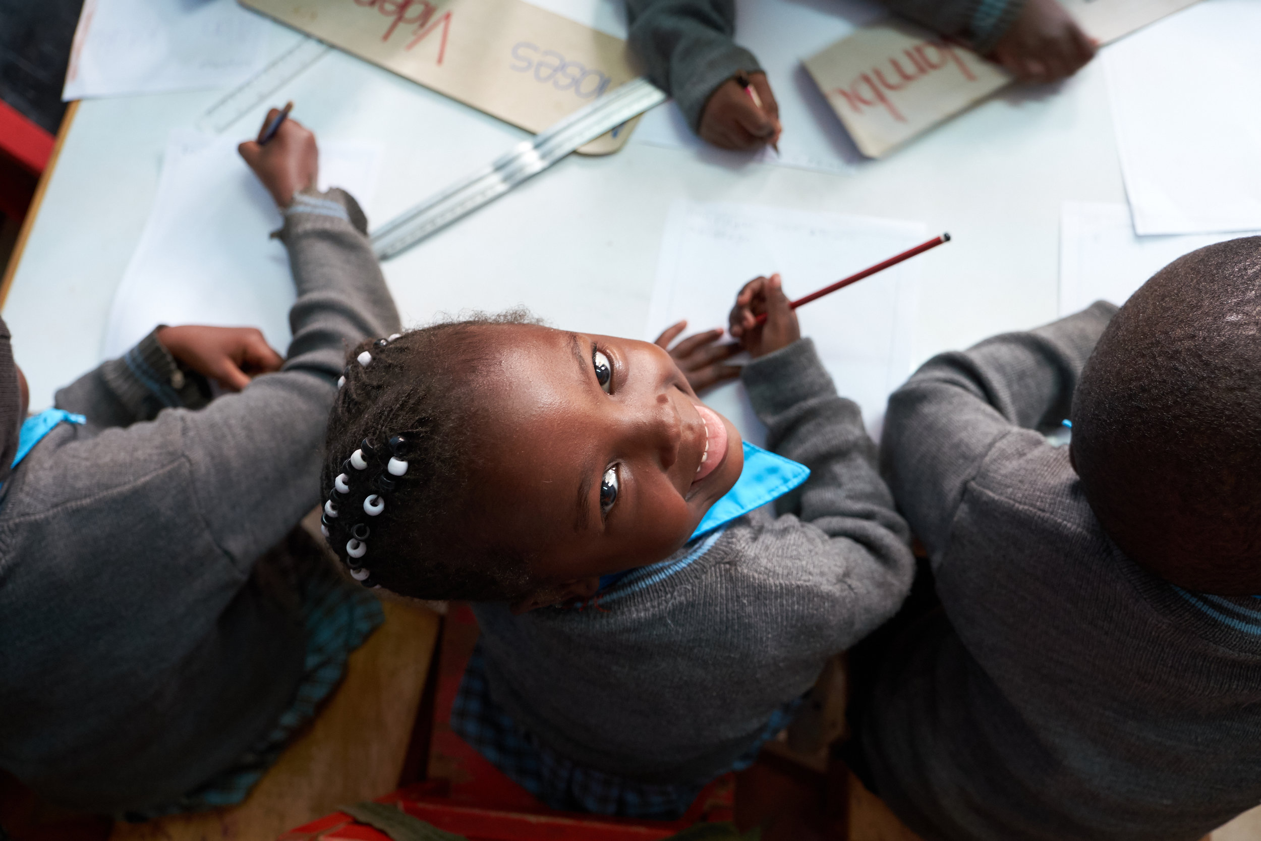 A student gleefully practices writing her name at Kidogo's Kawangware ECD hub.