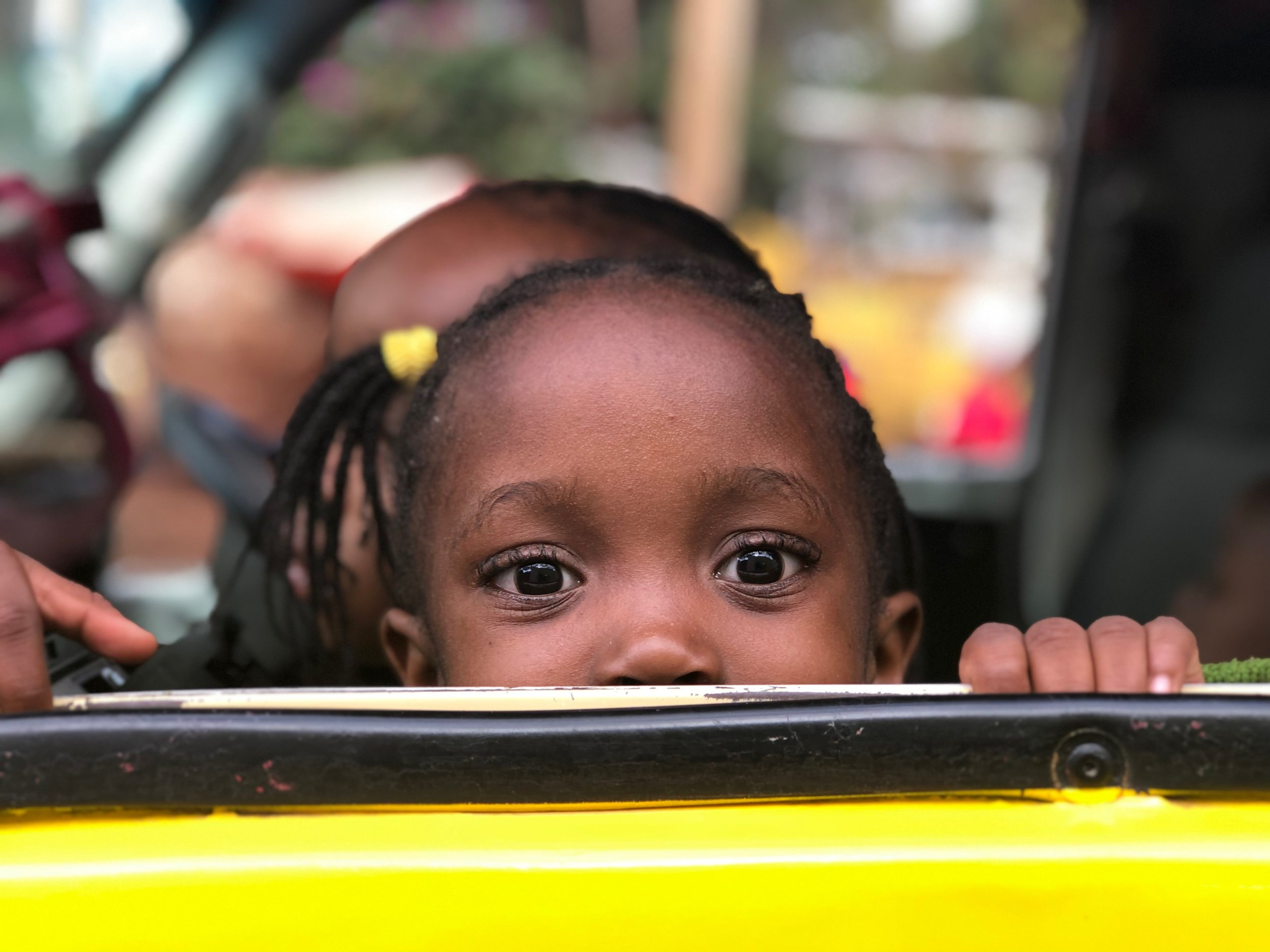 A young girl peaks over a car window as she leaves Sunflower to go home at the end of the day.