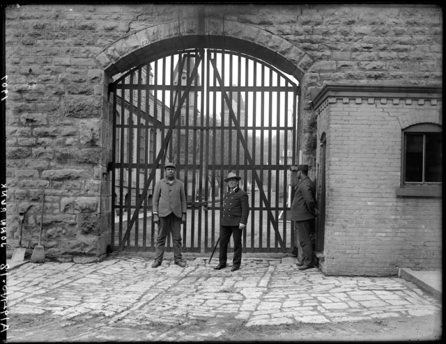"""This photo was taken by John Runk in 1907. It is the front gate of the Territorial prison which was located on the west side of Main Street. The image shows the guard and two trustees outside the gate.   To View a """"Time-Tunnel"""" photo of this same location that allows you to travel from 1907 to 2016, just click or tap on the above photo."""