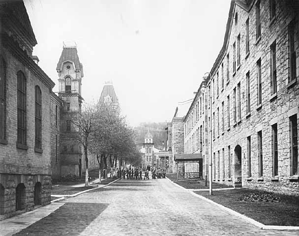 """The year is 1907. This is a photo by John Runk viewing west on the main road inside the prison. The prisoners are moving from a work area to their cells. In the rear is the infirmary of the prison. Photo courtesy of The Stillwater Public Library, John Runk Collection.   To view a """"Time-Tunnel"""" that takes you from 1907 to 2016 at this same location, Click or Tap on the photo above."""