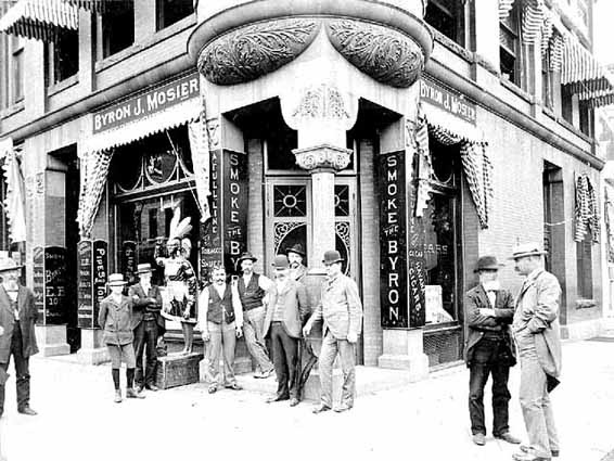 """This is the Byron J Mosier Building on the NE corner of Chestnut and Main Street. The building was a tobacco shop in the earliest days. It was also a bakery. Presently it is Leo's Malt Shop, another favorite place to enjoy a lively, good and quick meal. Photo credit, Mr. John Runk, courtesy of the Stillwater Public Library. The tobacco shop was famous for the wooden cigar store icon, which now resides in the Minnesota History Museum.   For a """"Time-Tunnel"""" experience from the turn of the century to the year 2016, just Click or Tap on the above photo."""