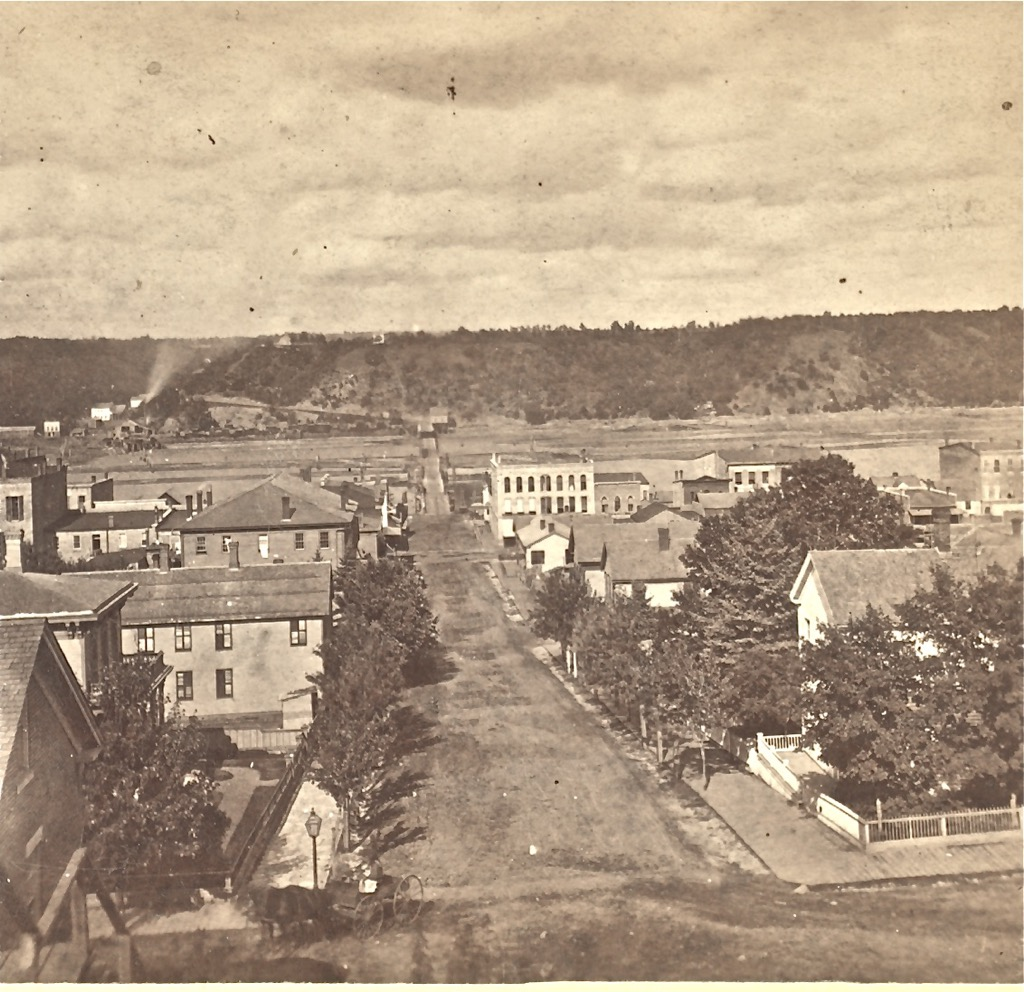 """This vantage point is from the Chestnut Street Stairway, taken in the 1870's by John Sinclair. You can see the first bridge in the background along with a lumber mill on the Wisconsin side of the St. Croix River. In the left center, you can see the Brunswick House and the brick building to the left of the stairway. This was before the streetcars first came to Minnesota. Photo courtesy of the Washington County Historical Society and Mr. Brent Peterson, executive director, WCHS.   To view a """"Time-Tunnel"""" photo of this same location from the 1870's to 2016, just Click or Tap the above photo."""