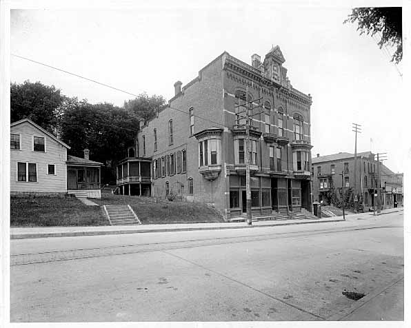 This is the Jassoy Building located on 3rd Street and Chestnut. It was built in 1886. It is a three-story frame red brick veneer with a Queen Anne Style. It has a flat roof and a stone banding between the floors along with bay windows on the second floor. This building still stands today at the base of the Chestnut Street Stairway. The streetcar tracks are visible in the foreground. The date of the photograph is 1918. Photo credit is Mr. John Runk, courtesy of The Stillwater Public Library, John Runk Collection.