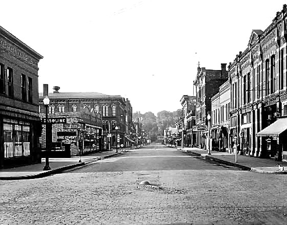 """View to the south on Main Street from Commercial Street. To the right is the Excelsior Building which still stands today.   To view this same location via the """"Time Tunnel"""" photo, just Click or Tap on the photo above."""