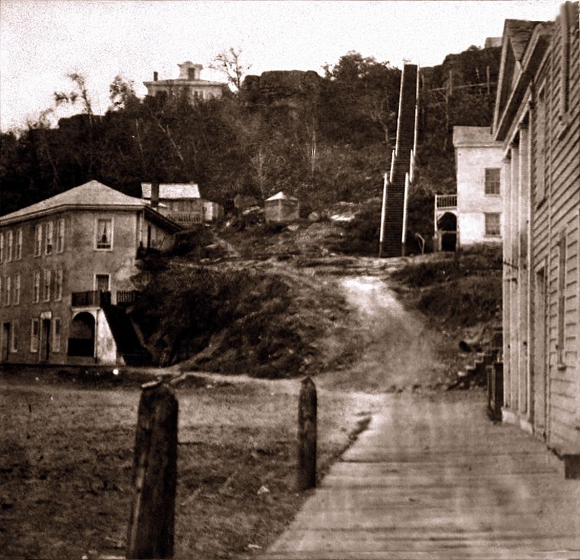 This is a very early (1866) view up the south hill stairs. The stairs were wooden at this time and it was before the construction of the brewery of Joseph Wolf. The home at the top of the hill still stands today. The three story building at the street level is gone.