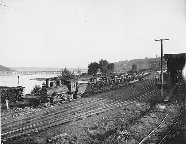 This is a John Runk photo taken behind the Northwest Thresher Manufacturing Company Building ca.1910. The view is toward the south with the wooden pontoon bridge in the background. Access to the railway was important to Stillwater during and after the lumber era.