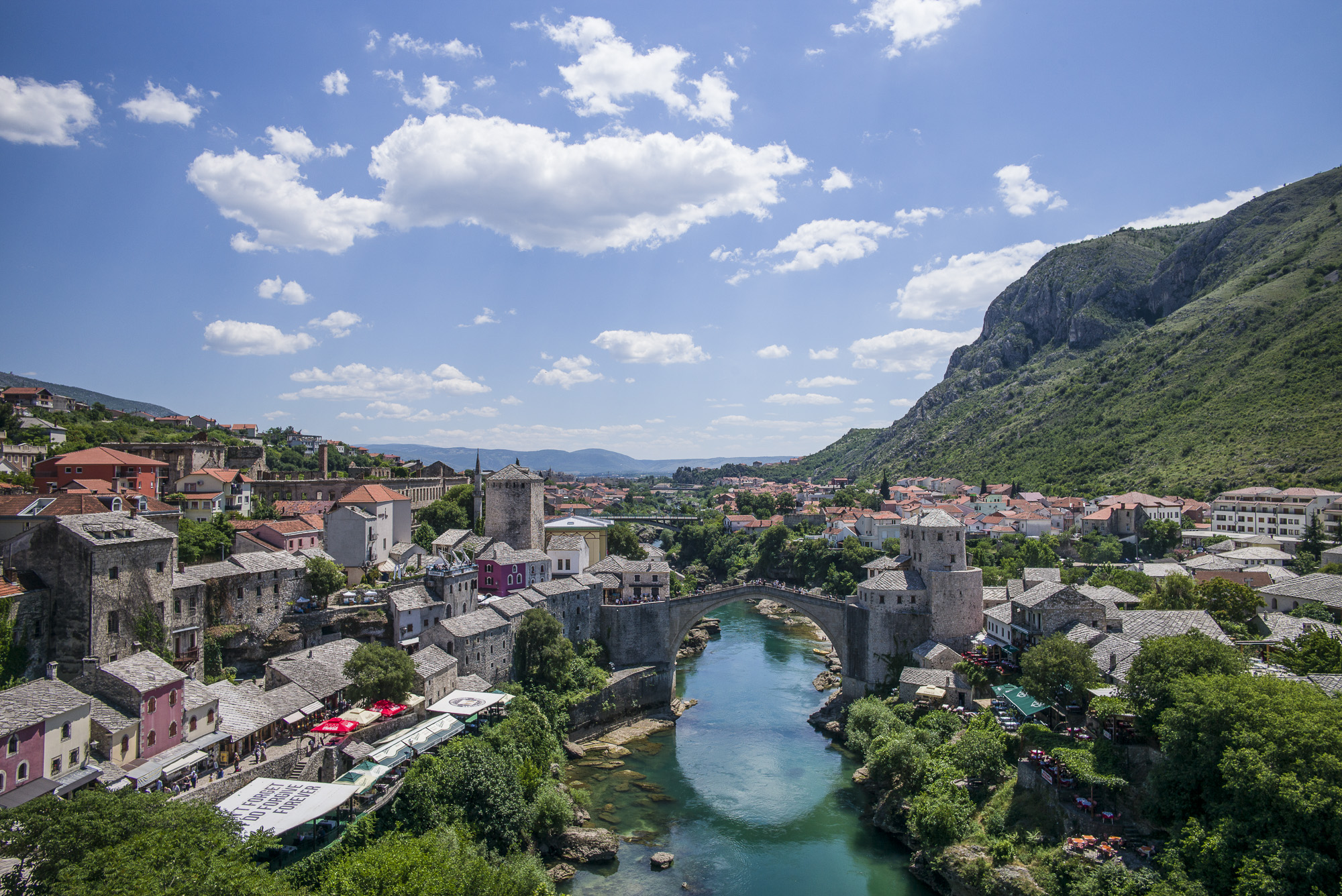 """The Mostar bridge (Stari Most) over the Neretva River. Note the sun shade, """" I DON""""T FORGET, I DO FORGIVE, FOREVER"""