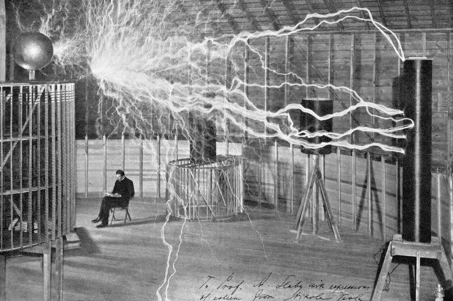 Nicola Tesla reading in a room of lightning