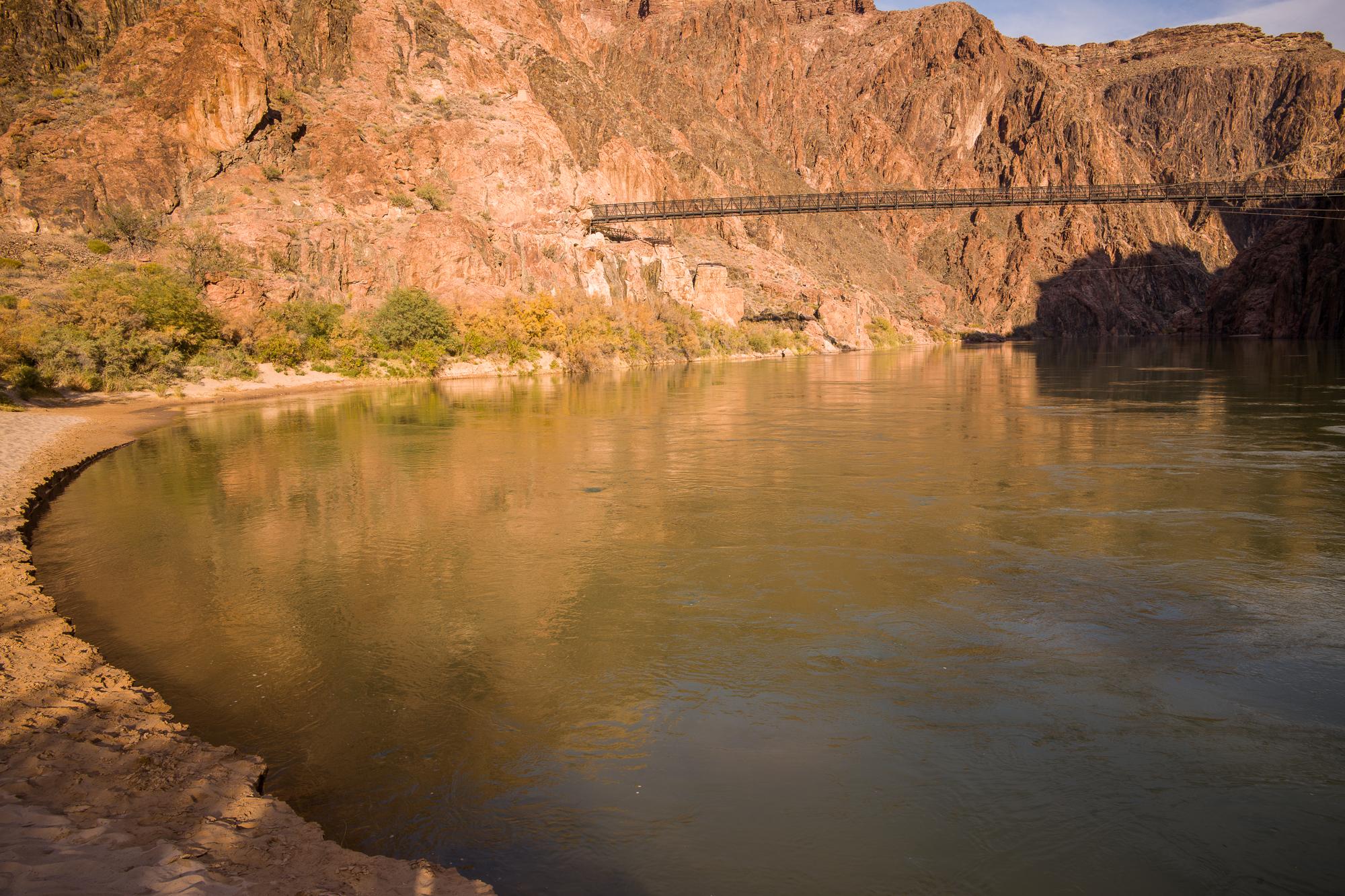 The black suspension bridge over the river