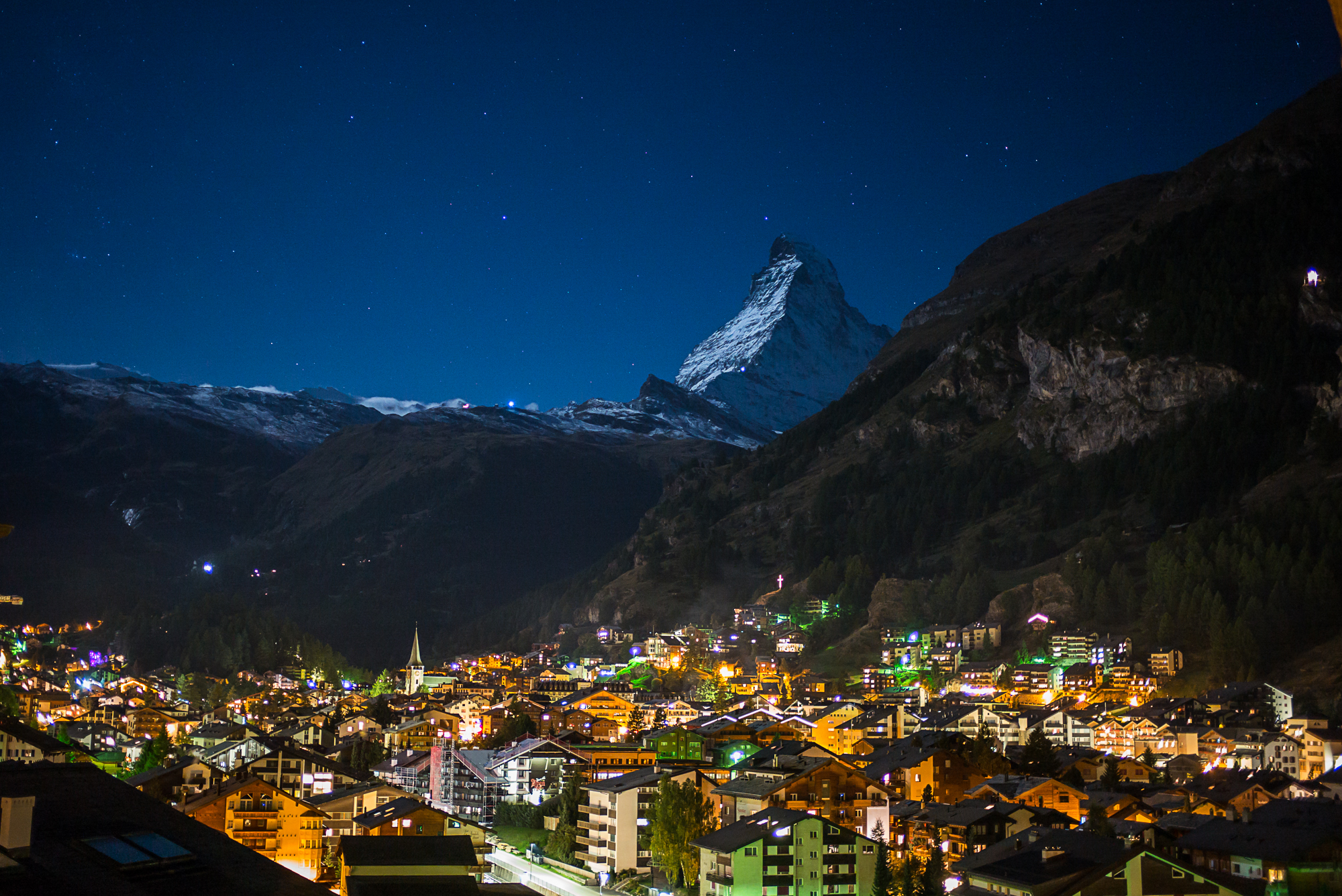Zermatt Village at night. The lights of the Edelweiss Chalet can be seen on the cliffs on the upper right of the photo