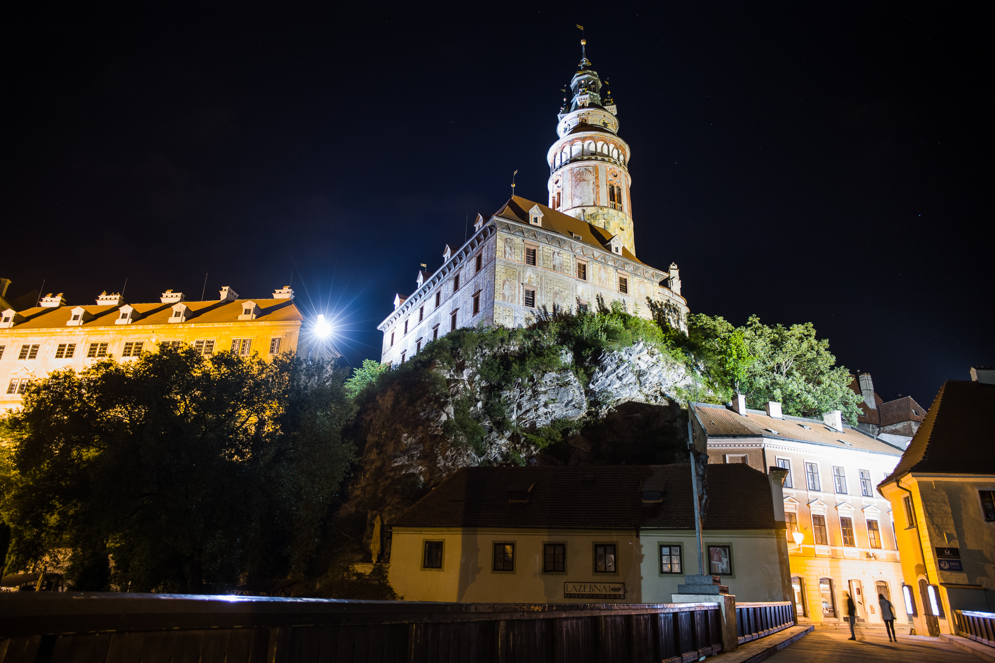 Česky Krumlov castle at night as seen from a bridge crossing the Vltava River in the old town